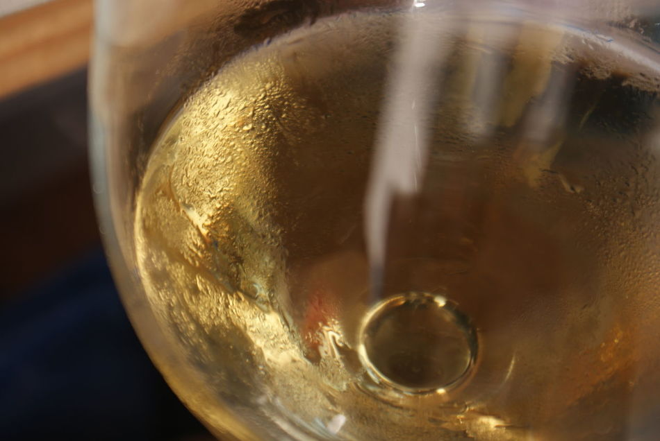 White wine in a glass glows golden and reflects sunlight outdoors in the winter afternoon. Afternoon Light Alcohol Beads Of Water Chardonnay Close-up Condensation On Glass Day Drink Gold Light Natural Light No People Outdoors Reflection Refreshment Sunlight Unedited Photo Wine Wine Moments Wineglass