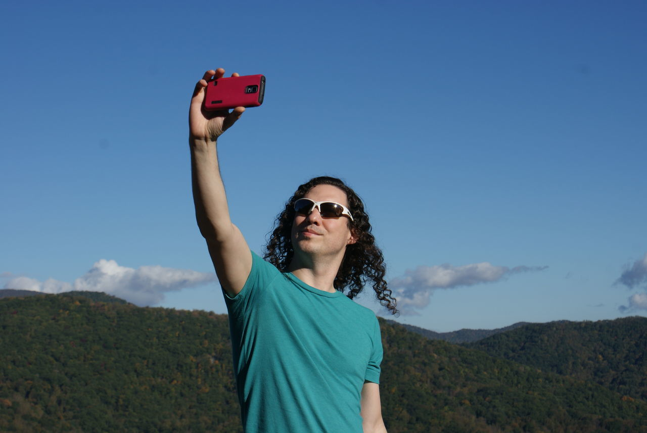 A young man in sunglasses holds his cellphone up for a selfie against the wide blue sky and green mountains of the Blue Ridge Parkway. Blue Blue Sky Casual Clothing Day Landscape Man Mountain Mountain Range Nature Outdoors Portrait Scenics Selfie Sky Sunglasses Tshirt Vacation Photo Vacations Young Adult EnjoytheNewNormal