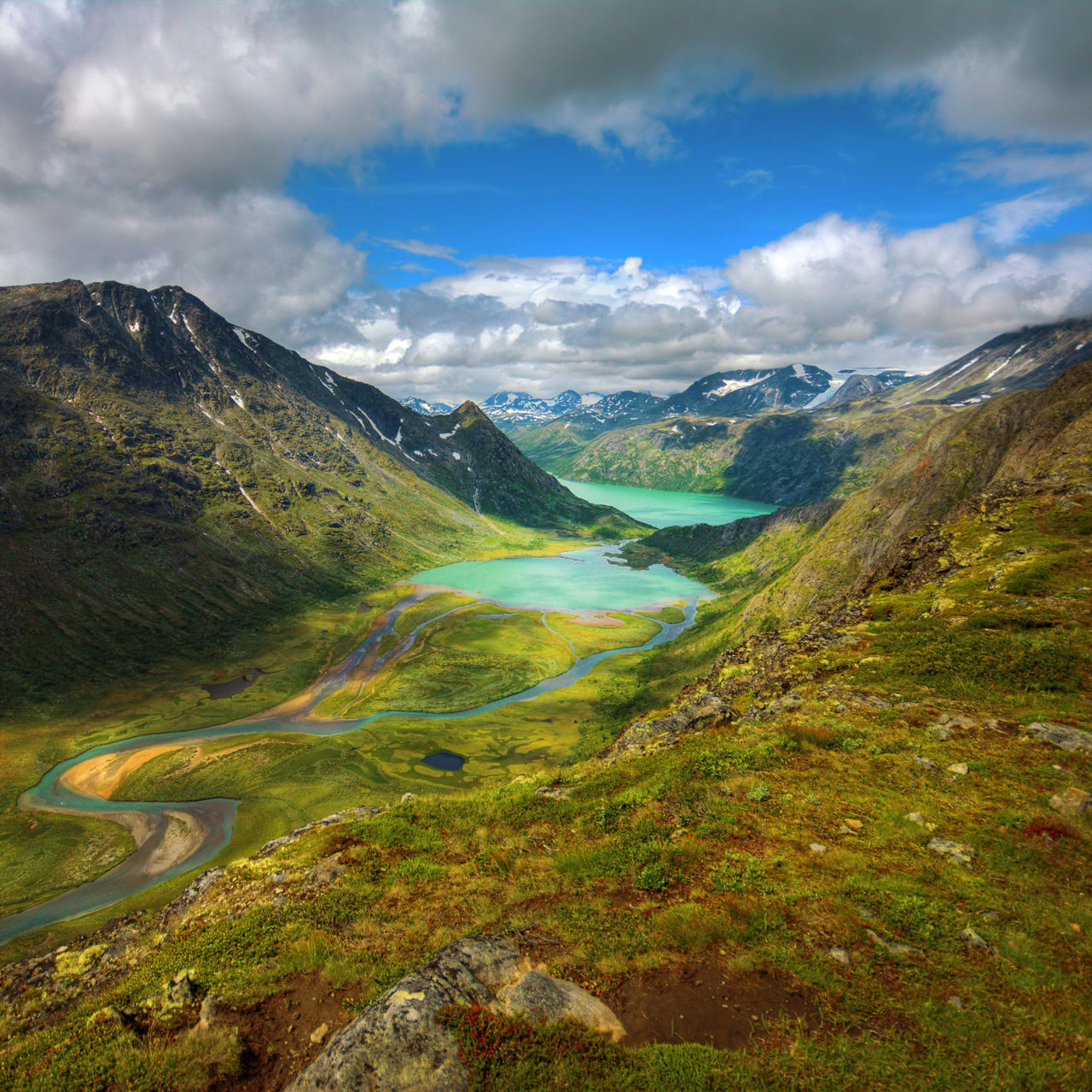 High Angle View Of River Amidst Mountains Against Cloudy Sky