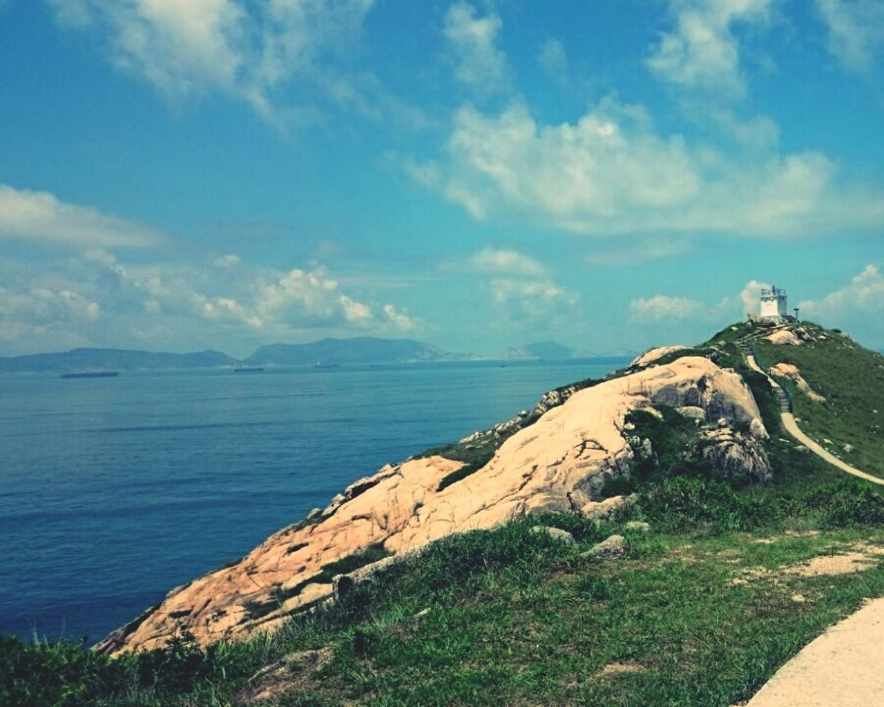 scenics, nature, beauty in nature, tranquility, mountain, tranquil scene, sea, outdoors, day, no people, sky, grass, water