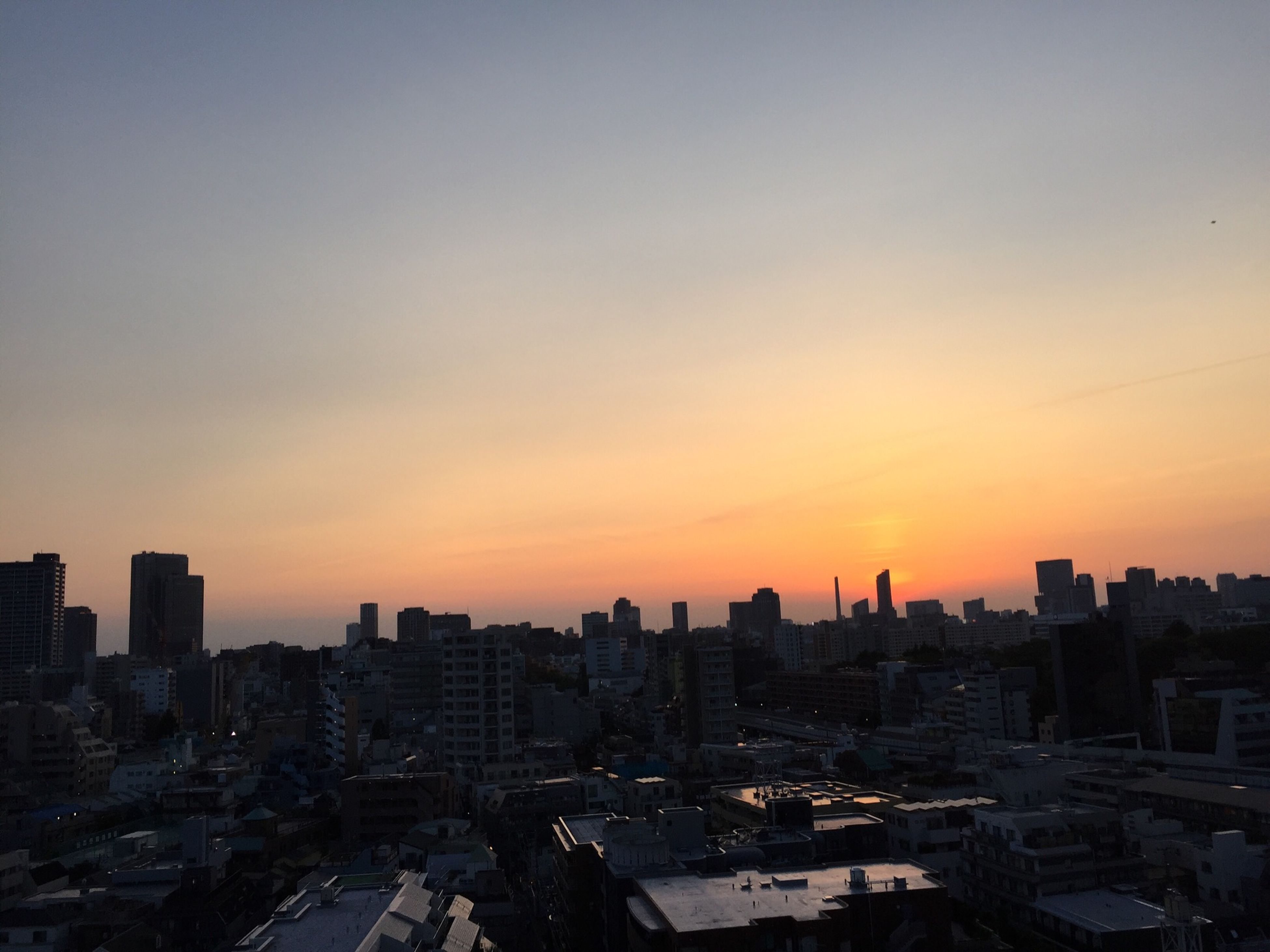 city, building exterior, cityscape, architecture, sunset, built structure, high angle view, orange color, copy space, skyscraper, crowded, residential district, city life, clear sky, residential building, tower, tall - high, sky, residential structure, urban skyline