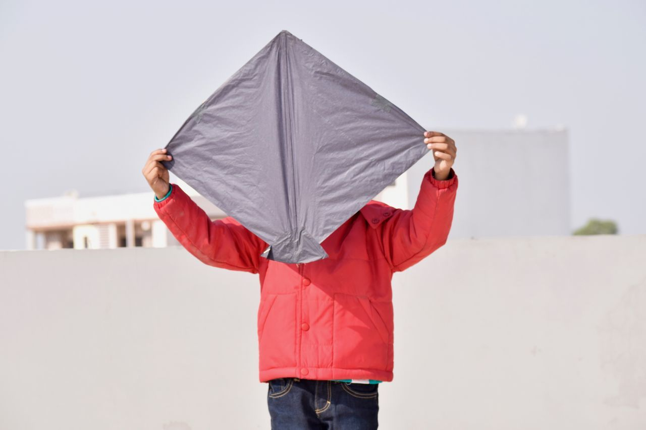 A Kid Ready for Flying Adult Childhood Day Front View Hiding Holding Hood - Clothing Makar Sankranti,India One Person Outdoors People Portrait Red Sky Standing Vacations Kites Kitesurfing