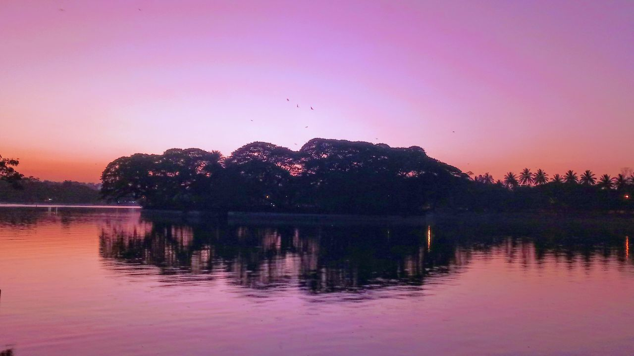 reflection, lake, water, sunset, nature, beauty in nature, scenics, tranquil scene, silhouette, tranquility, waterfront, tree, sky, no people, outdoors, clear sky, mountain, day