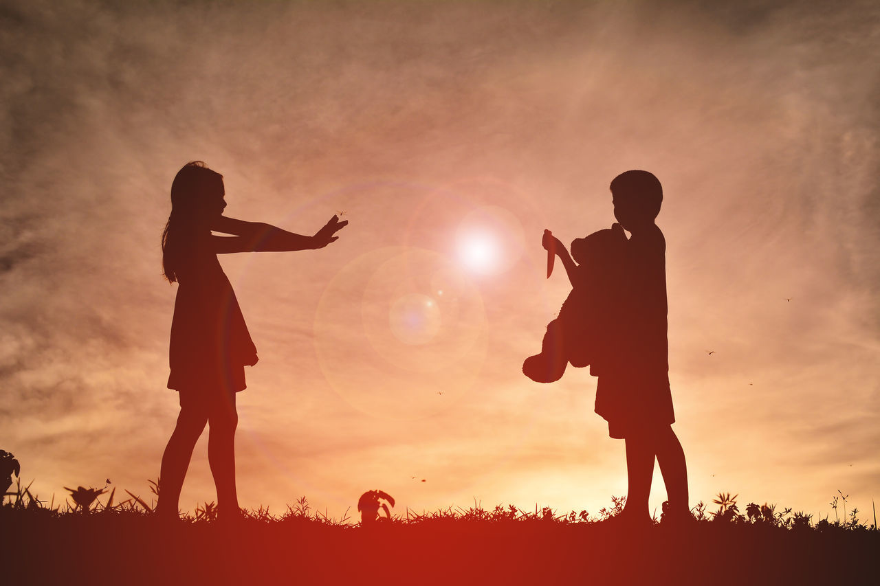 sunset, silhouette, real people, sun, leisure activity, togetherness, men, lifestyles, standing, orange color, sky, nature, outdoors, low angle view, friendship, field, full length, beauty in nature, bonding, women, day, people