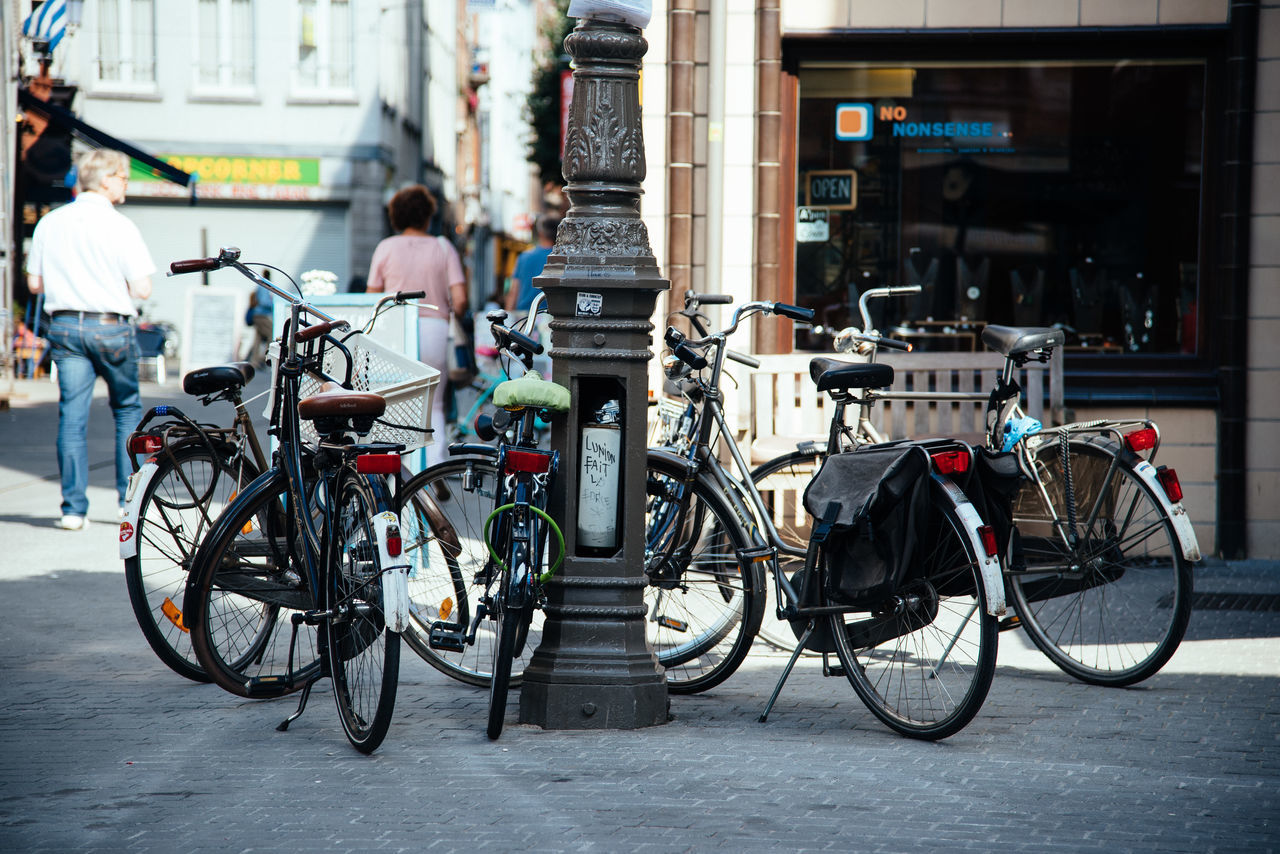 bicycle, mode of transport, transportation, street, building exterior, architecture, built structure, real people, city, land vehicle, outdoors, city life, day, men, stationary, one person, people
