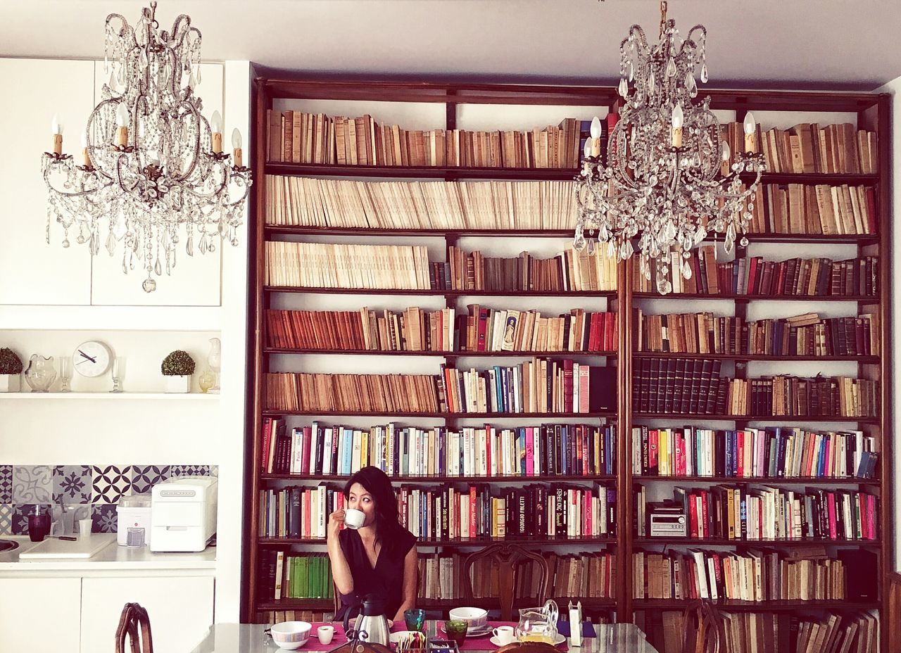 Woman Drinking Coffee Against Book Shelves At Home