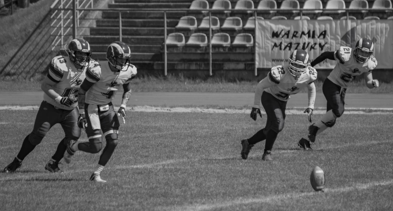 American Football - Ball American Football - Sport American Football Player American Football Team American Football Uniform Competition Competitive Sport Day Full Length Helmet Leisure Activity Outdoors Playing Playing Field Real People Running Sport Sports Clothing Sports Helmet Sports Team Sportsman Team Sport Teamwork Young Adult Young Men
