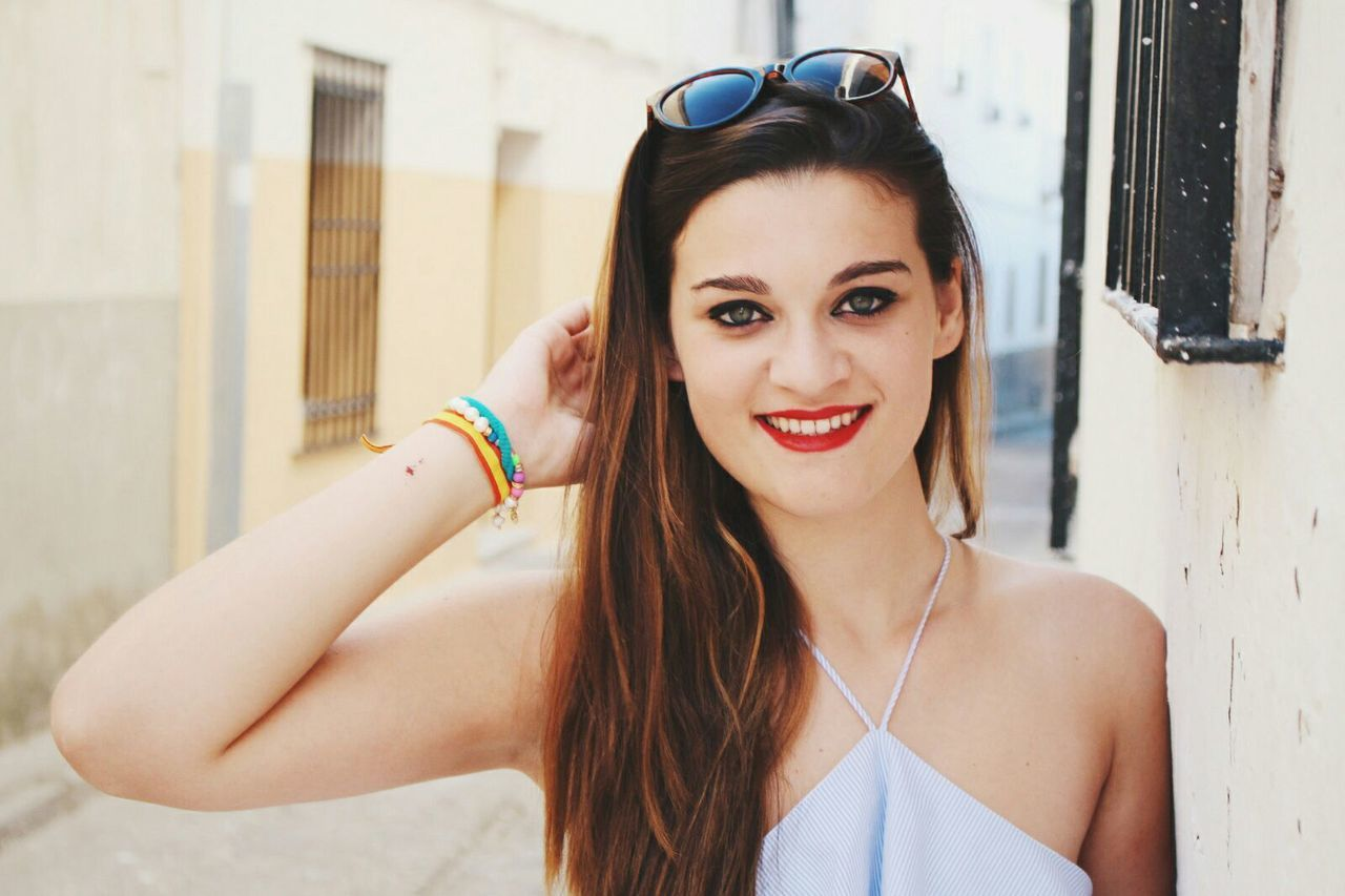 looking at camera, one person, young adult, young women, real people, portrait, long hair, front view, beautiful woman, day, smiling, fashion, outdoors, lifestyles, focus on foreground, leisure activity, headshot, happiness, tank top, standing, built structure, headband, building exterior, close-up