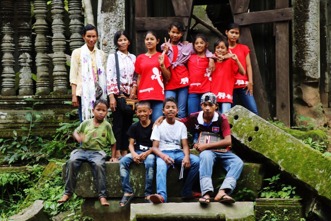 boys, childhood, sitting, medium group of people, full length, front view, girls, smiling, mid adult, outdoors, enjoyment, day, elementary age, child, cultures, women, fun, portrait, togetherness, young adult, cheerful, architecture, looking at camera, men, young women, happiness, building exterior, adult, people