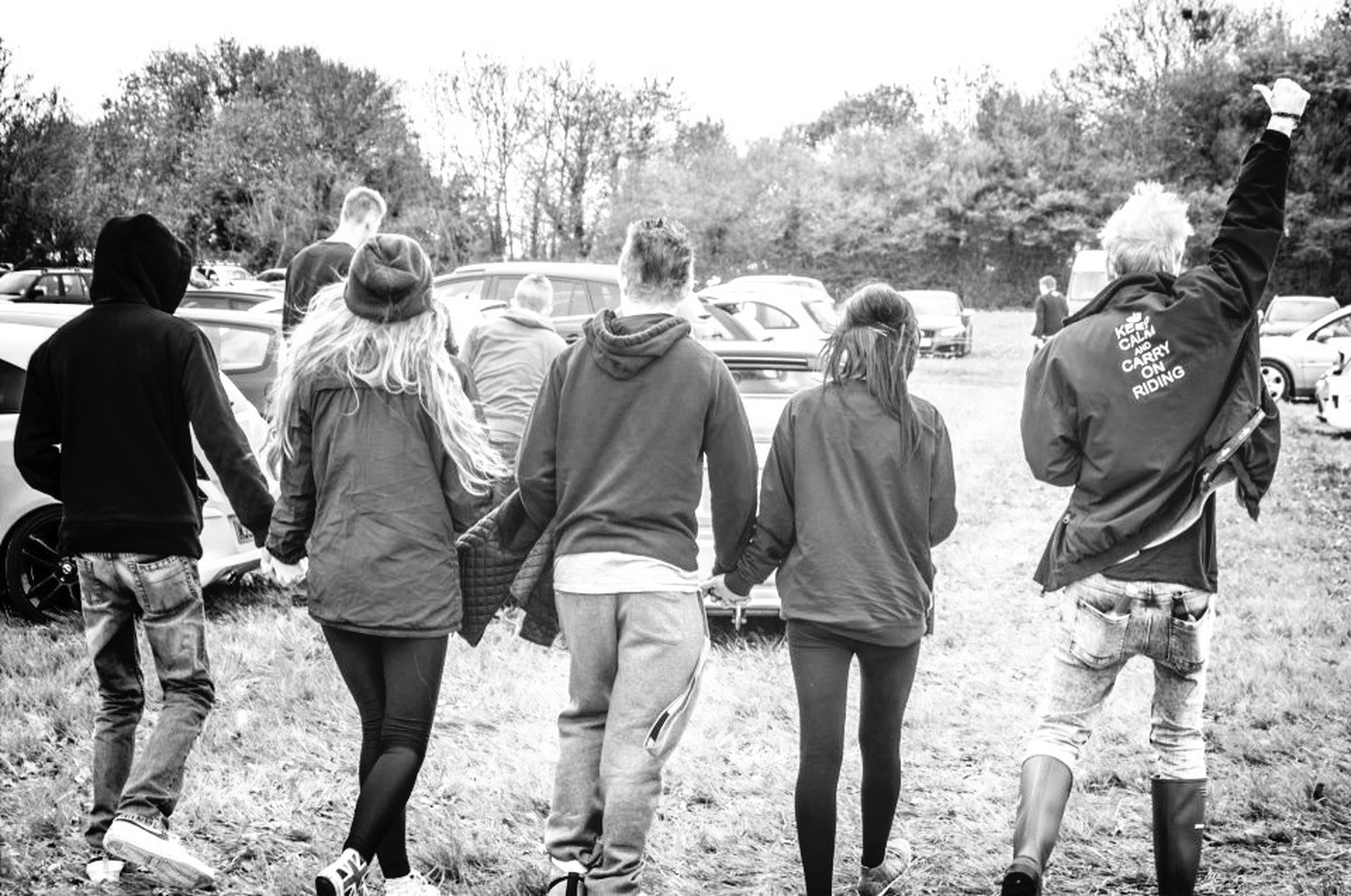 men, lifestyles, leisure activity, togetherness, casual clothing, person, rear view, walking, tree, large group of people, full length, standing, friendship, day, medium group of people, bonding, outdoors, animal themes