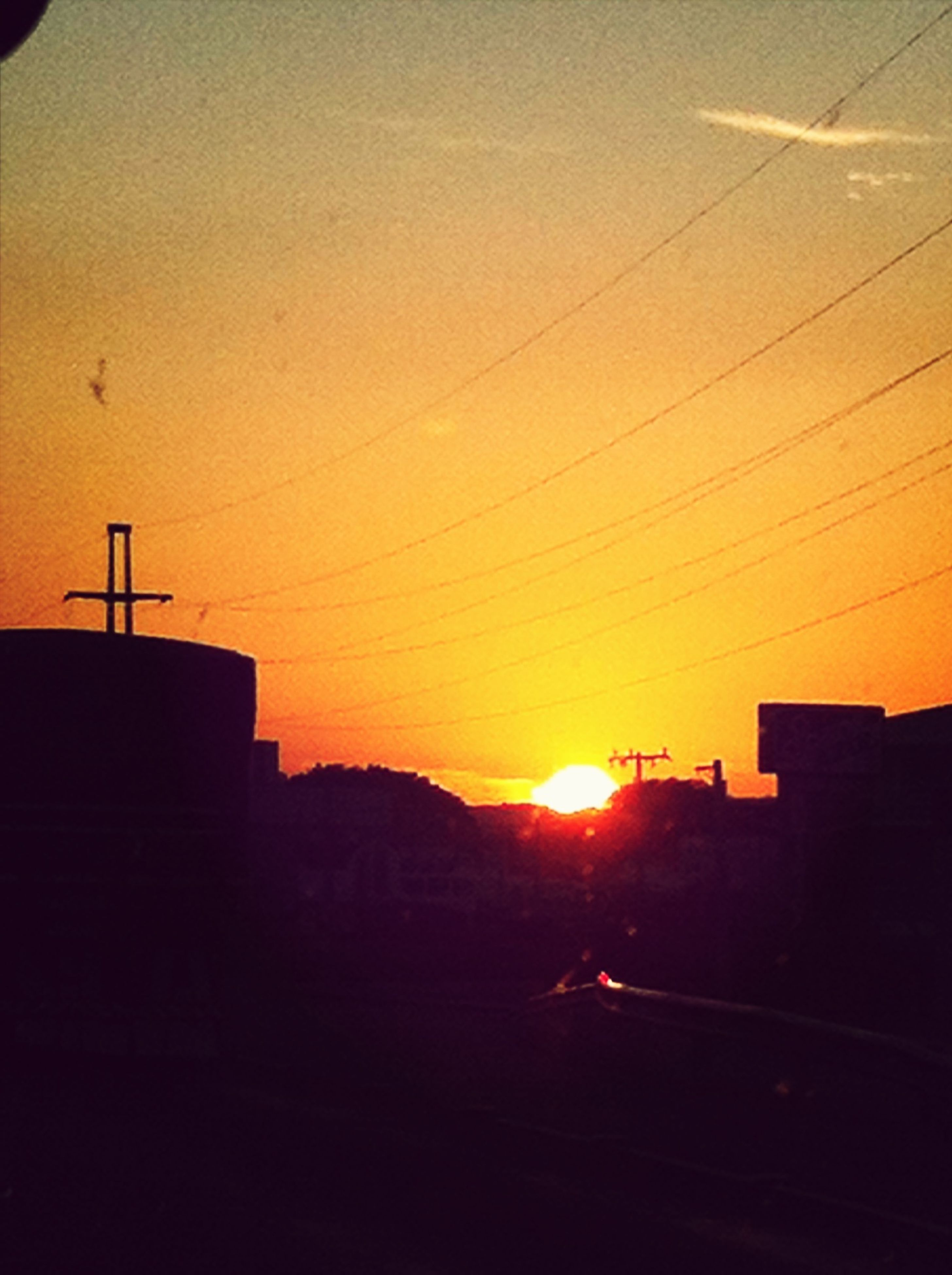 sunset, silhouette, sun, building exterior, orange color, built structure, architecture, sunlight, sky, power line, house, electricity pylon, nature, sunbeam, outdoors, beauty in nature, no people, city, residential structure, scenics