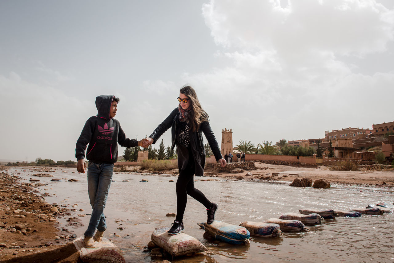 Boy helps Veronica cross the river to get to the old part of Ait Benhaddou city, Morocco. Connected By Travel Exploring Travel Travel Photography Adult Beach Casual Clothing Day Full Length Outdoors People Real People Sand Sky Togetherness Travel Destinations Two People Young Adult Young Women