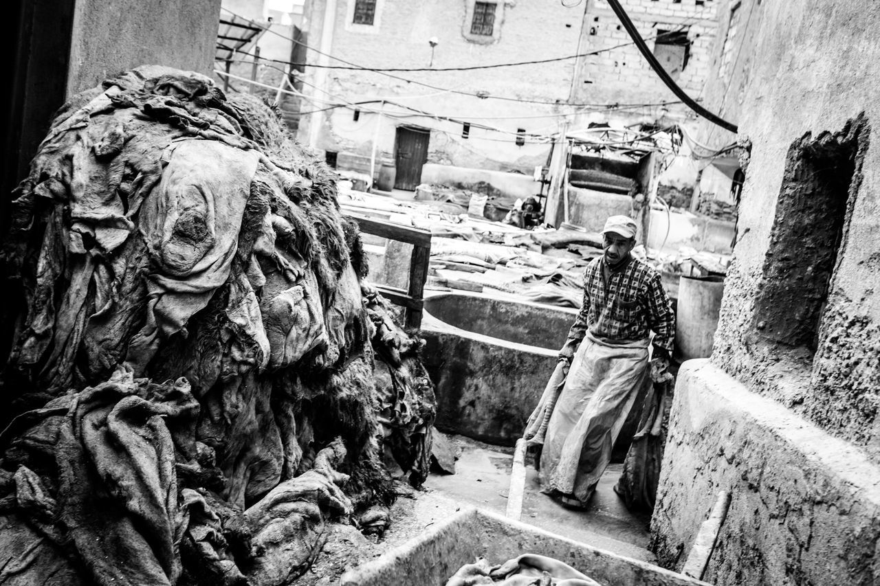 Worker Walking By Heap Of Clothes Against Building At Laundry