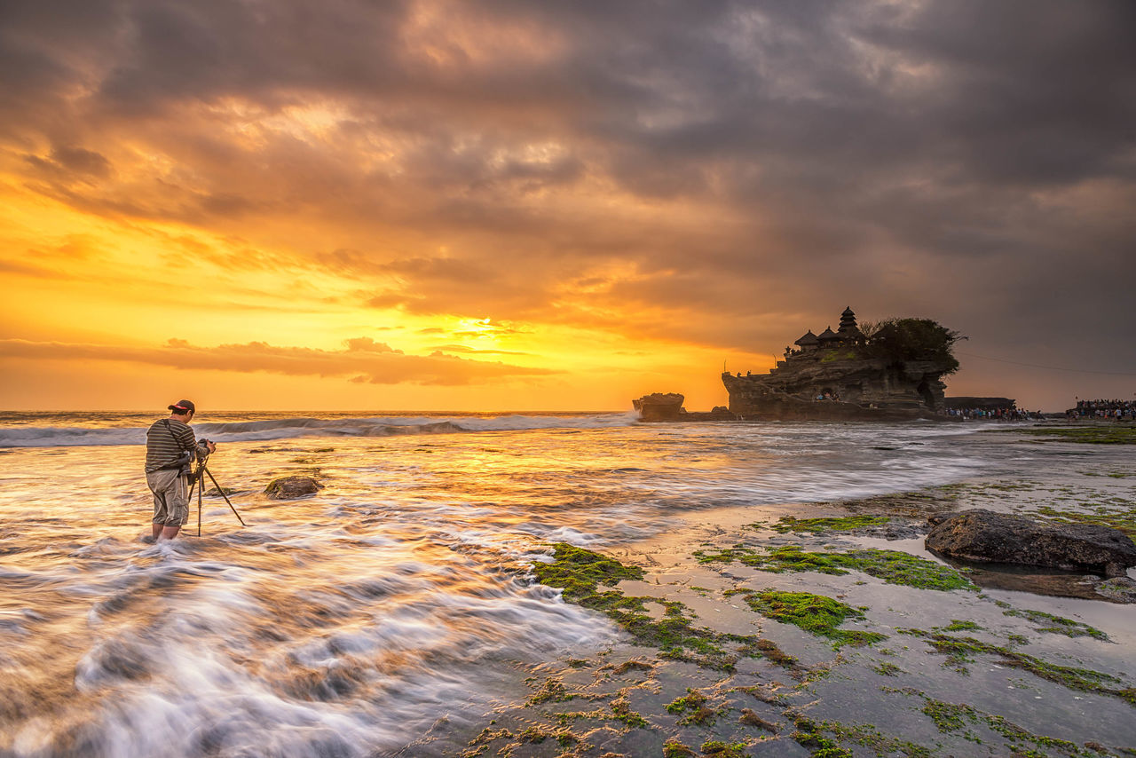 A photographer photographing Sunset at Tanah Lot, a popular tourist attraction in Bali, Indonesia. Architecture Bali Beach Clouds Clouds And Sky Cloudscape Hobby INDONESIA Island Moss Nature Outdoors Photographer Pura Rock Formation Sea Sunset Sunsets Tanah Lot Temple Tourist Tourist Attraction  Travel Travel Destinations Waves