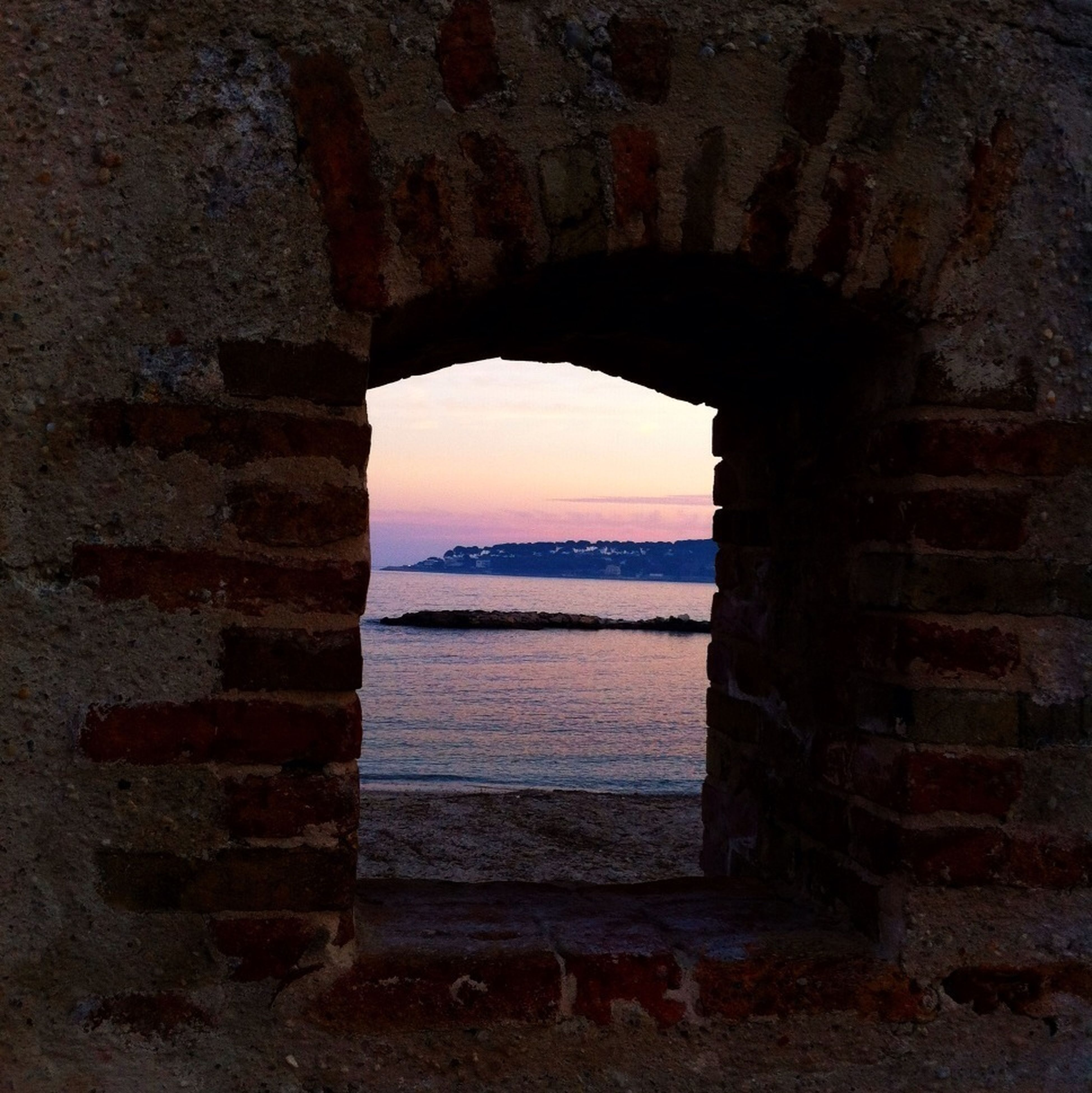sea, built structure, water, architecture, arch, horizon over water, sky, tranquility, indoors, old, sunset, beach, nature, rock - object, scenics, weathered, stone wall, abandoned, tranquil scene, no people