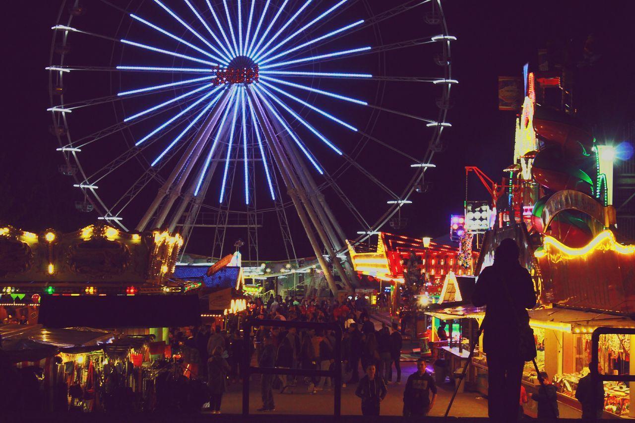 arts culture and entertainment, leisure activity, amusement park, night, illuminated, amusement park ride, ferris wheel, real people, large group of people, enjoyment, men, outdoors, fun, sky, people