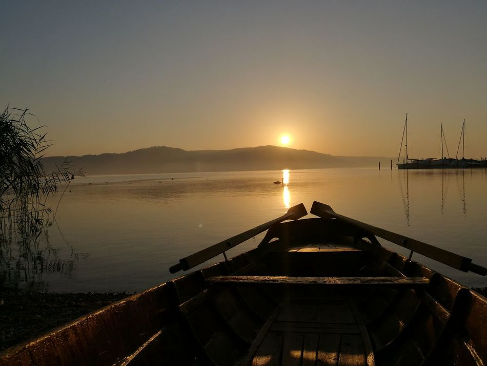 Transportation Nautical Vessel Boat Mode Of Transport Sunset Water Sun Tranquil Scene Scenics Lake Moored Tranquility Reflection Beauty In Nature Nature Mountain Sunbeam Calm Orange Color Non-urban Scene