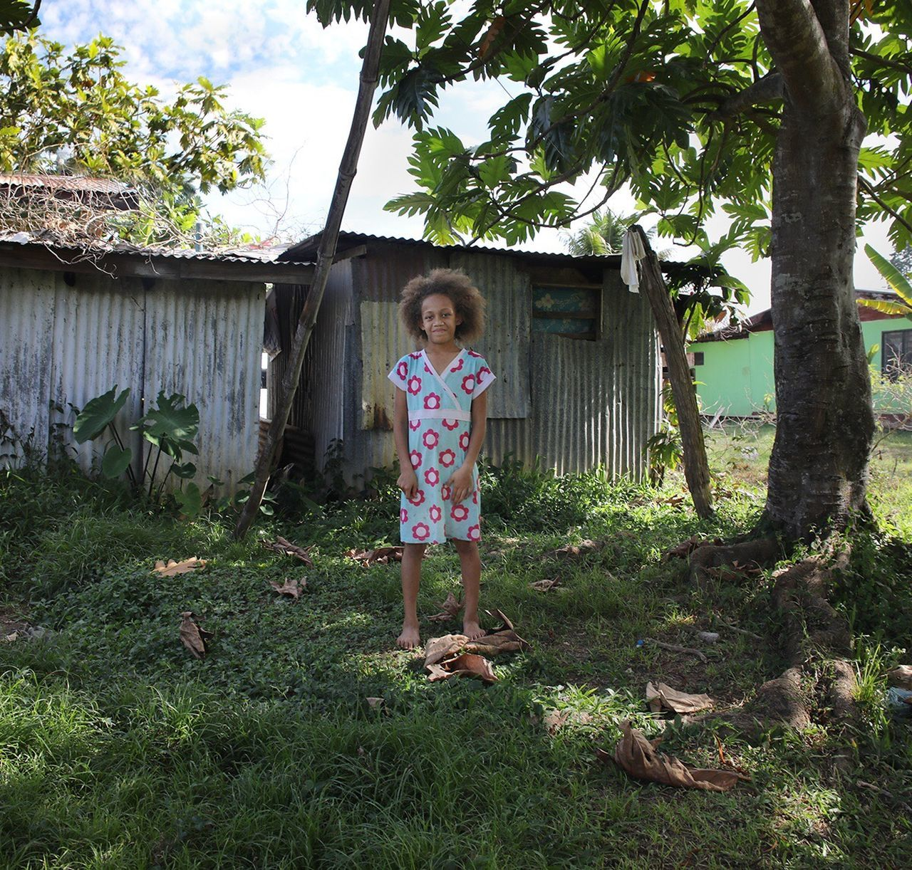 one person, looking at camera, real people, full length, house, portrait, childhood, day, girls, smiling, standing, casual clothing, happiness, growth, leisure activity, tree, elementary age, lifestyles, outdoors, playing, grass, building exterior, architecture, people