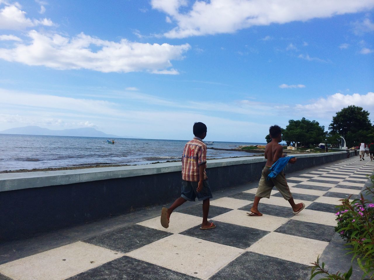 Rear View Of Boys Walking On Tiled Walkway By Sea Against Sky