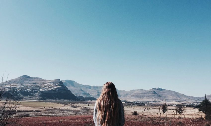 Earth. Mountain Rear View Copy Space Day Clear Sky Landscape Nature One Person Long Hair Field Blue Mountain Range Beauty In Nature