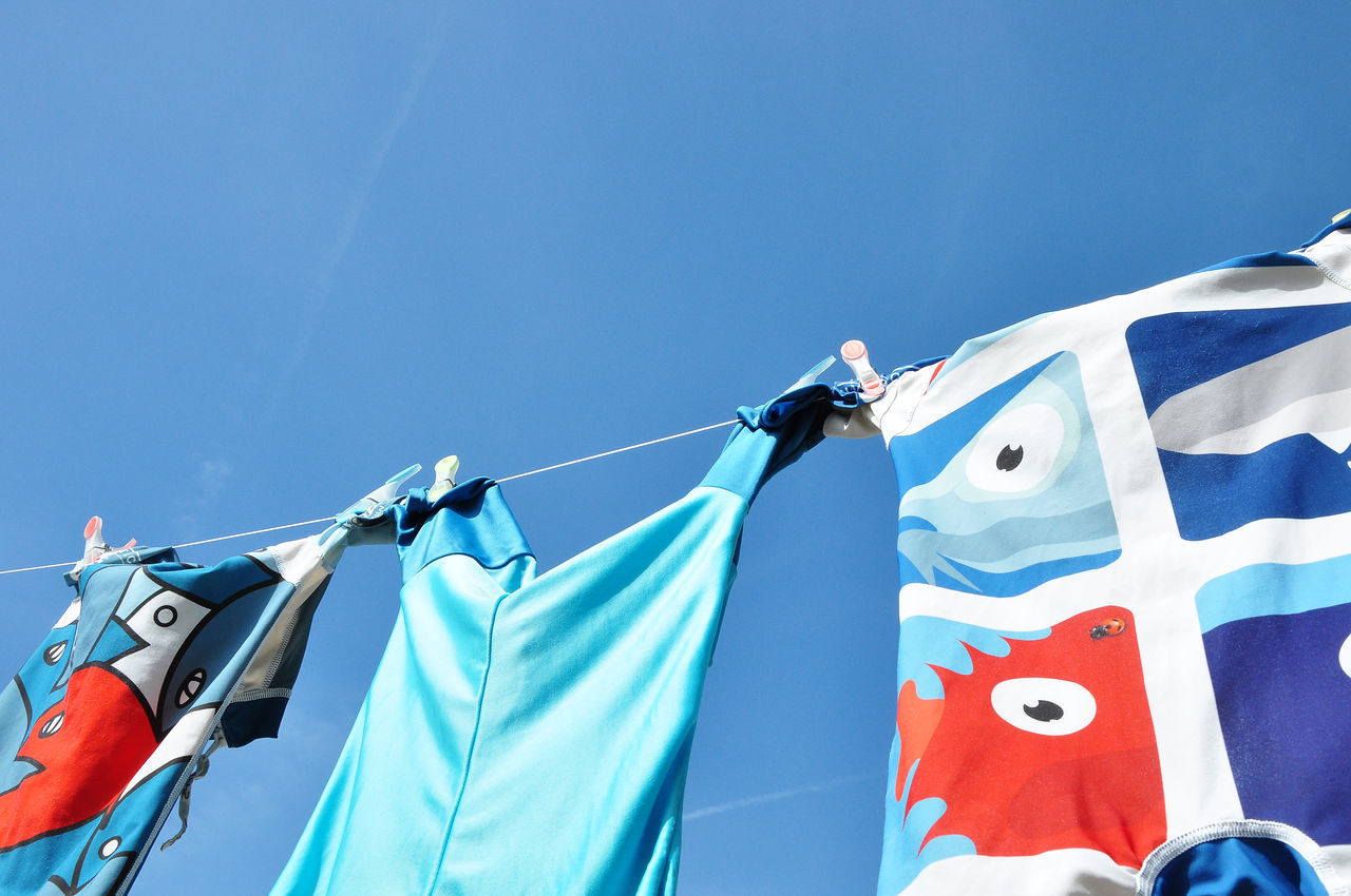 Three Swimsuits On Clothes Line Baby Clothing Blue Clear Sky Close-up Clothesline Clothespin Clothing Day Drying Hanging Horizontal Laundry Low Angle View Multi Colored No People Outdoors Photography Side By Side Sky Summer Sunlight Swimsuit