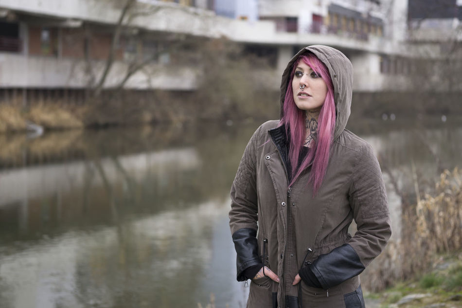 Bleak Casual Clothing Contemplation Copy Space Deprived Area Front View Girl Housing Estate Inked Lifestyles Neglected Neighborhood Person Piercing Pink Hair Portrait Real People River Standing Tattoo Woman Young Adult Young Women Youth