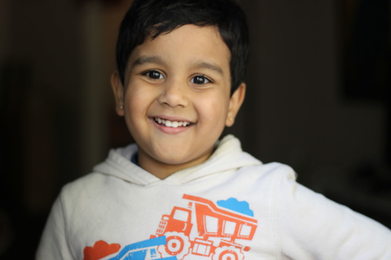 looking at camera, real people, portrait, smiling, one person, childhood, text, boys, focus on foreground, showing, happiness, elementary age, cheerful, close-up, indoors, day