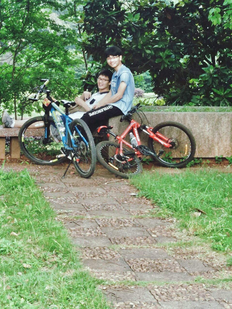 bicycle, transportation, two people, cycling, full length, riding, tree, togetherness, day, mode of transport, mountain bike, adventure, cycling helmet, nature, outdoors, real people, smiling, men, grass, friendship, young adult, people