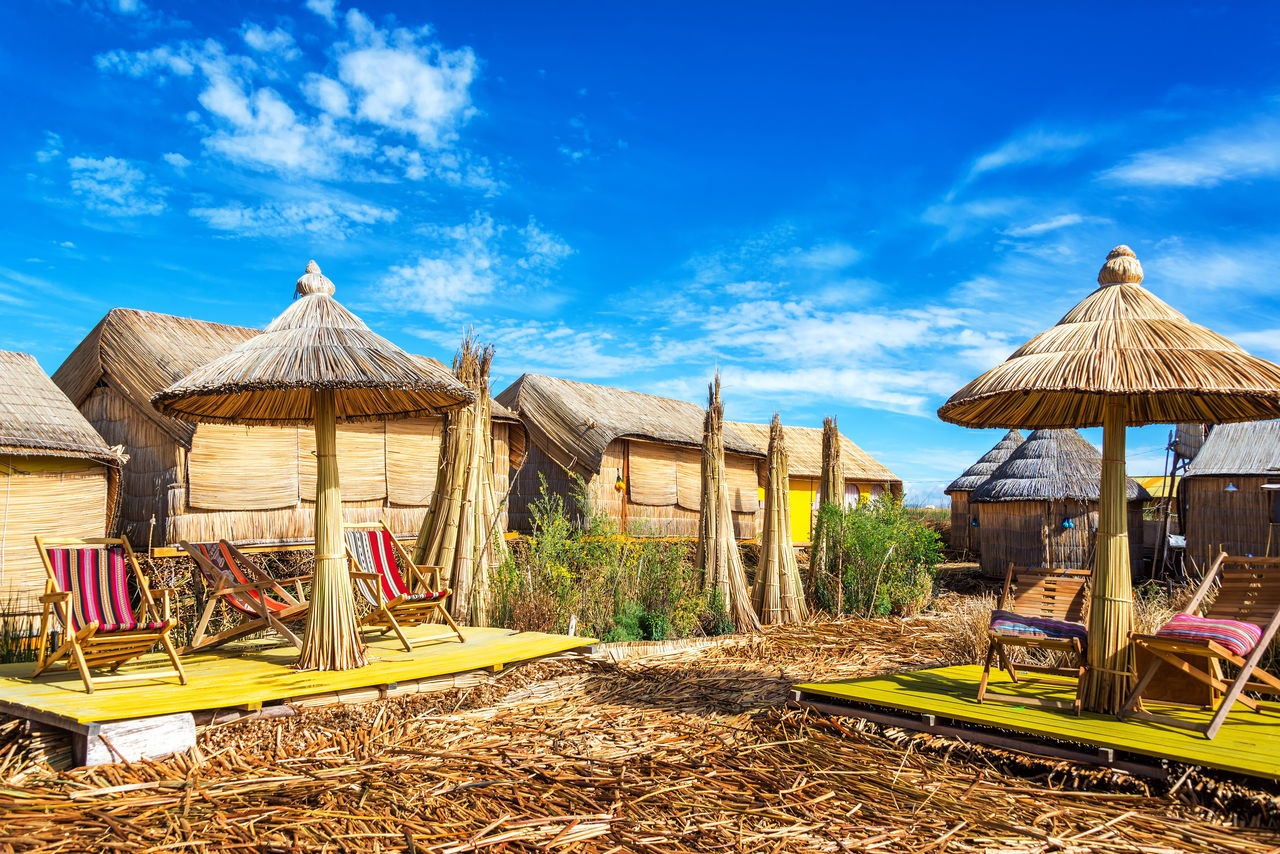 Houses and umbrellas made out of reeds on Uros floating islands on Lake Titicaca near Puno, Peru America Andes Boat Destination Floating Inca Lake Landscape Latin Native Nature Peru Peruvian Puno Puno, Perú Reed Scenic Sky Titicaca Titicaca Lake Totora Travel Uros Uros Island Water