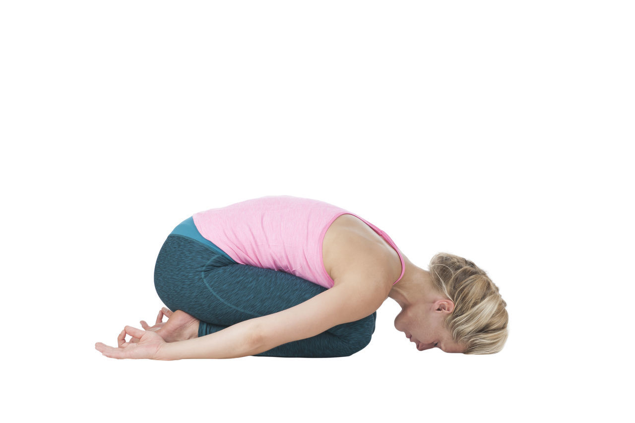 Side full body view of a young blond woman in the Yoga exercise position of the child (Garbhasana) on a white background. Adult Adults Only Blond Hair Challenge Effort Exercise Mat Exercising Flexibility Full Length Garbhasana Gymnastics Healthy Lifestyle Lifestyles One Person One Woman Only One Young Woman Only Only Women People Performance Position Of The Child Stretching Studio Shot White Background Young Adult Young Women