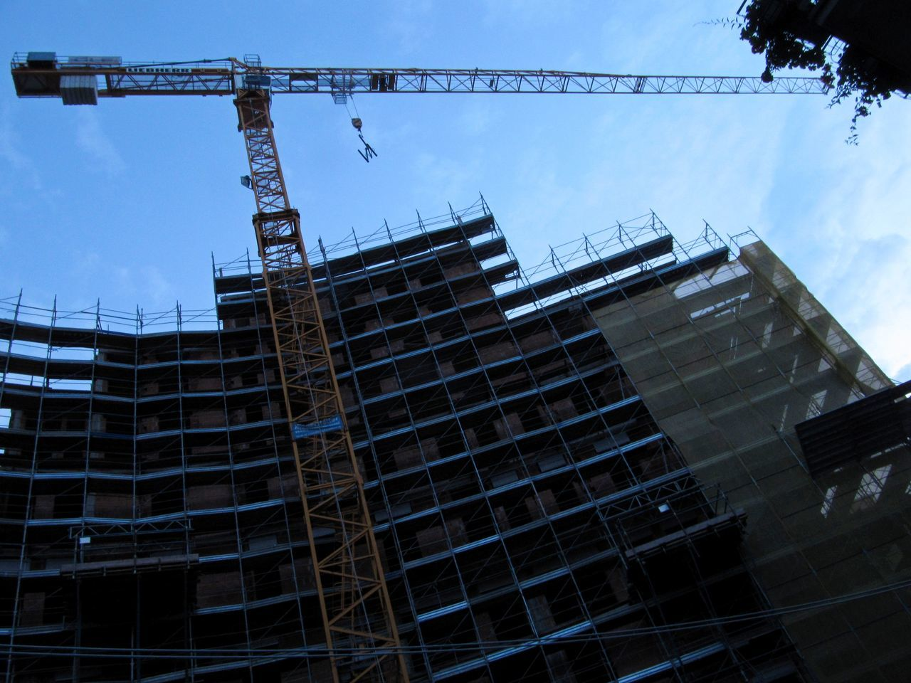 Low angle view of incomplete building and crane against blue sky