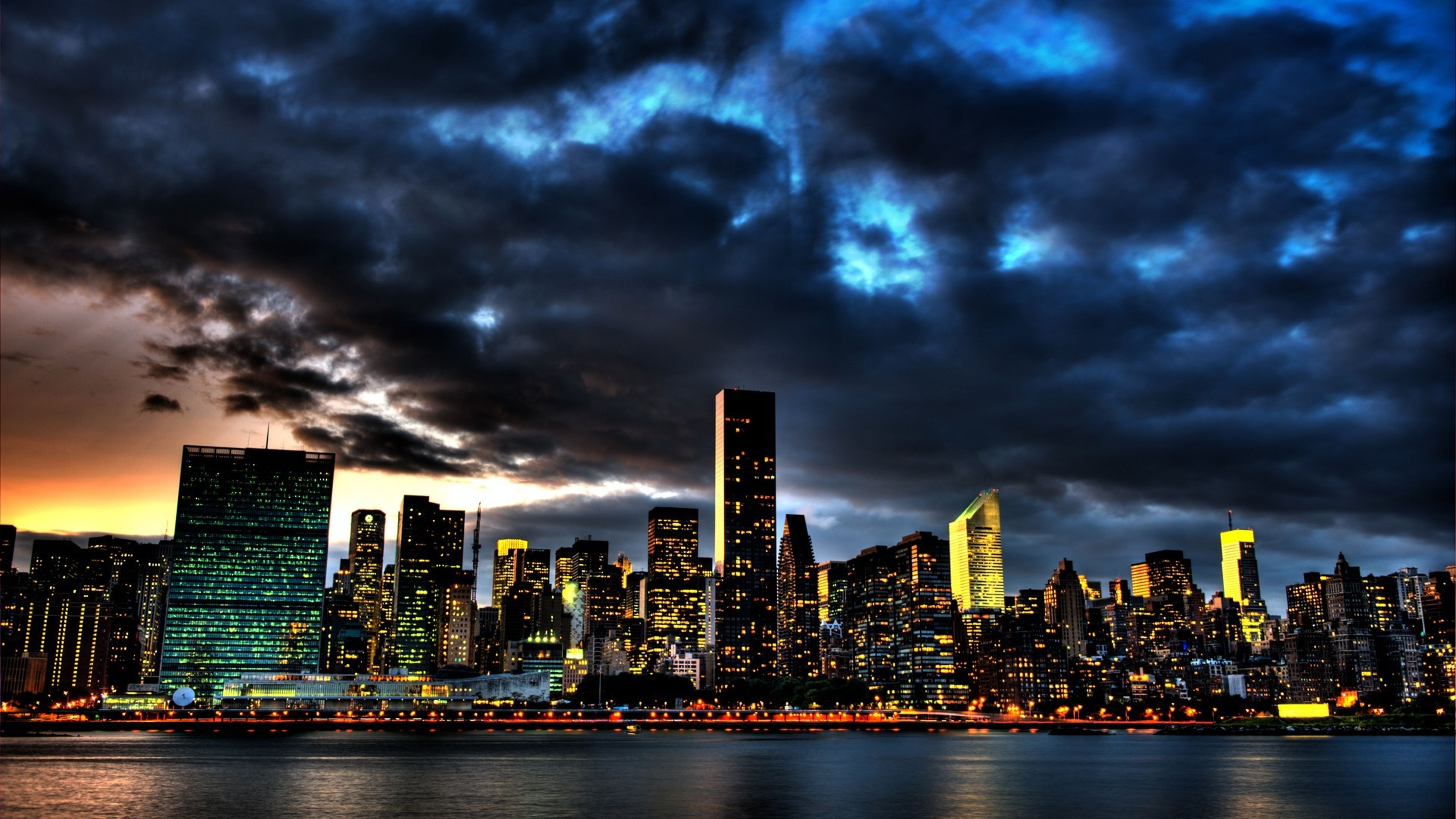 city, building exterior, architecture, cityscape, sky, built structure, cloud - sky, skyscraper, water, waterfront, illuminated, cloudy, urban skyline, modern, river, weather, storm cloud, dusk, skyline, tall - high