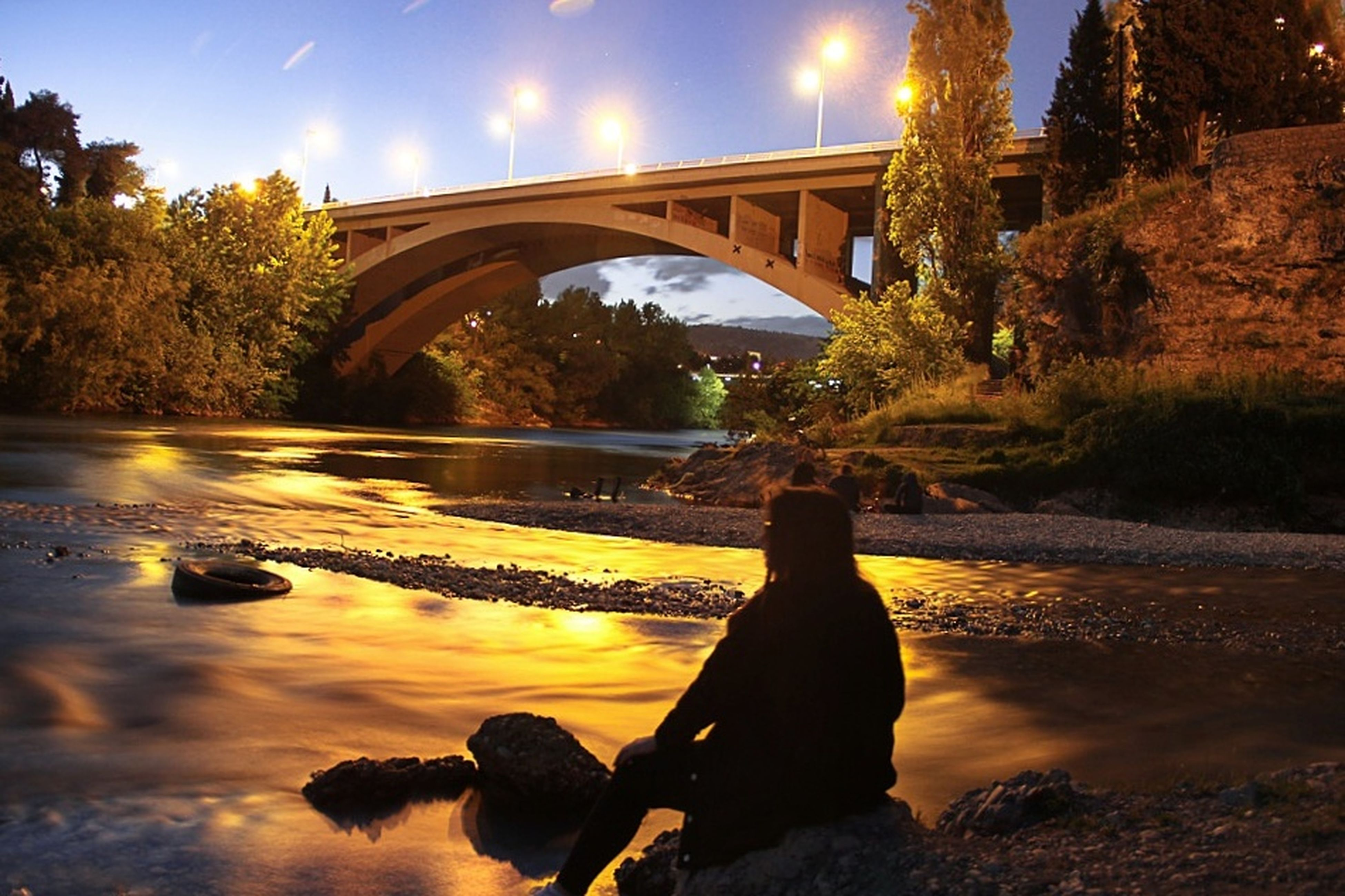 water, reflection, nature, tree, sunset, river, beauty in nature, bridge - man made structure, outdoors, sitting, sky, no people, day