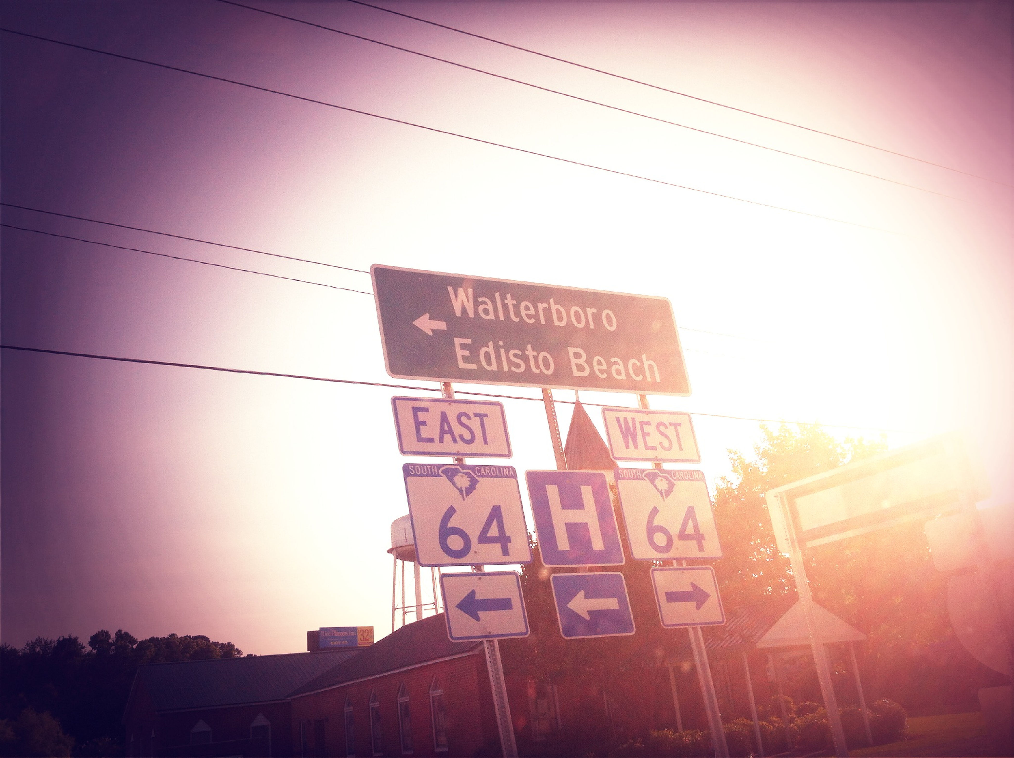 text, western script, communication, low angle view, information sign, sunset, guidance, information, non-western script, sign, capital letter, sky, clear sky, road sign, arrow symbol, sun, outdoors, no people, sunlight, directional sign