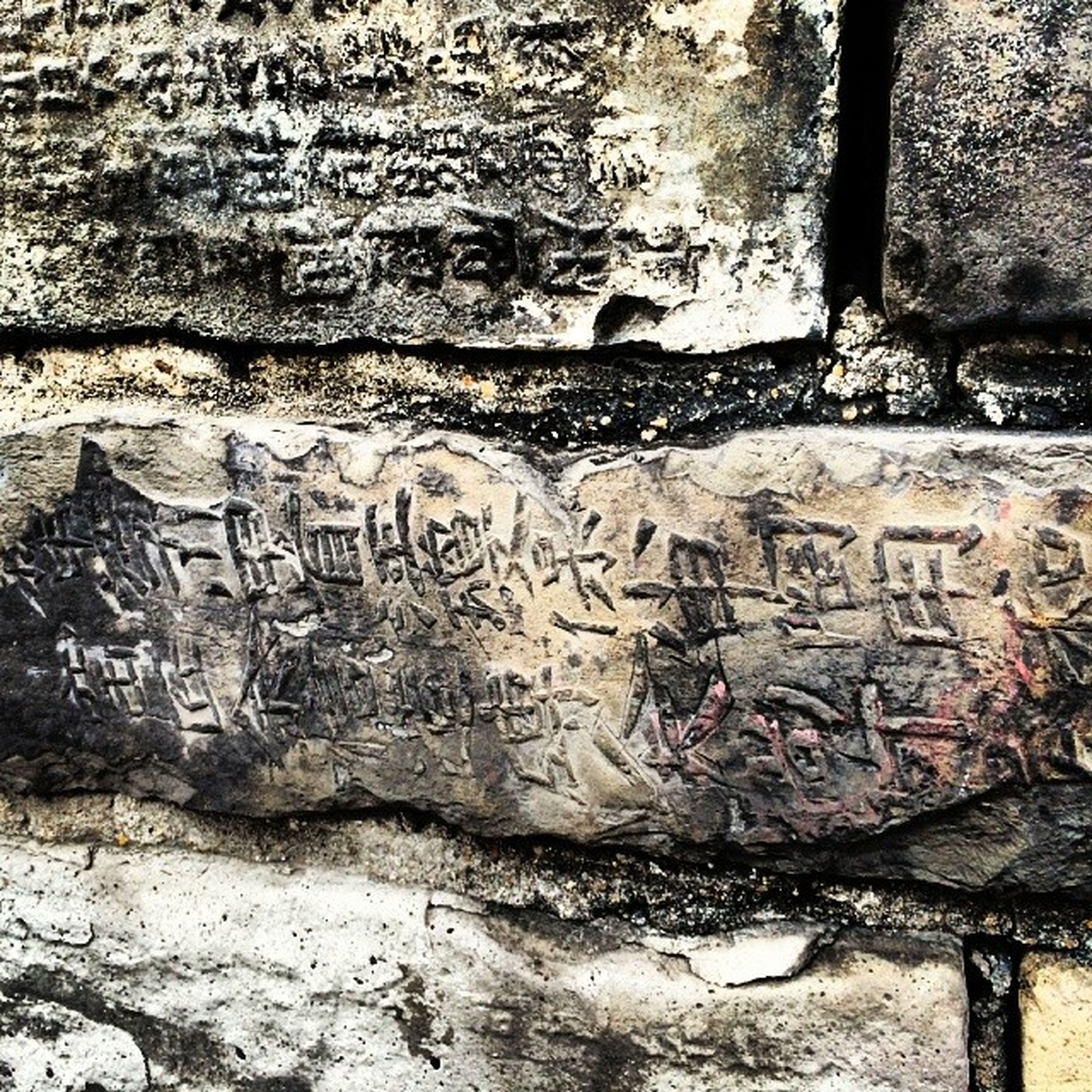text, western script, art, communication, art and craft, creativity, graffiti, wall - building feature, human representation, built structure, architecture, non-western script, old, weathered, textured, wall, day, capital letter, carving - craft product