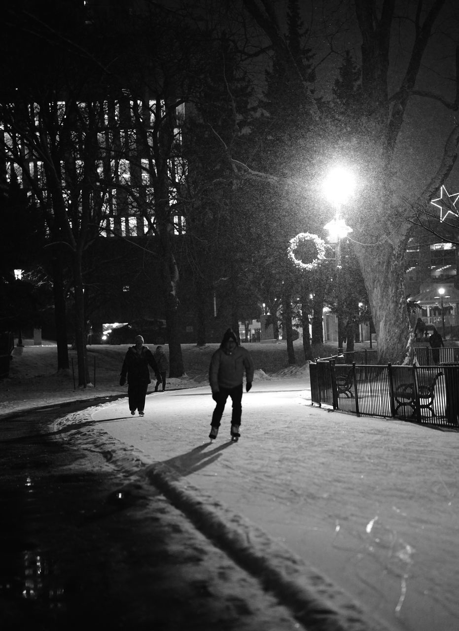 full length, real people, walking, winter, night, tree, built structure, outdoors, city, leisure activity, building exterior, lifestyles, architecture, men, cold temperature, snow, illuminated, nature, warm clothing, people