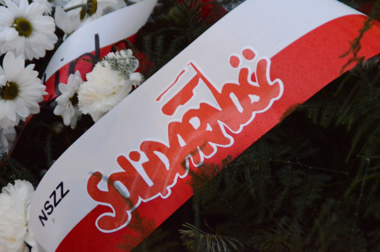 Flowers along with a banner Flag Flowers Memorial Poland Polish Solidarność Text Western Script