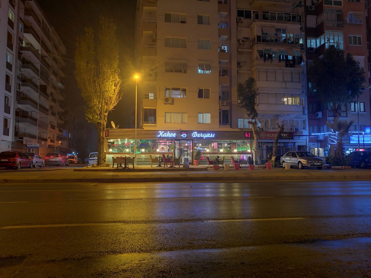 illuminated, night, building exterior, architecture, transportation, street, built structure, city, land vehicle, mode of transport, car, road, street light, outdoors, tree, real people, cityscape, sky