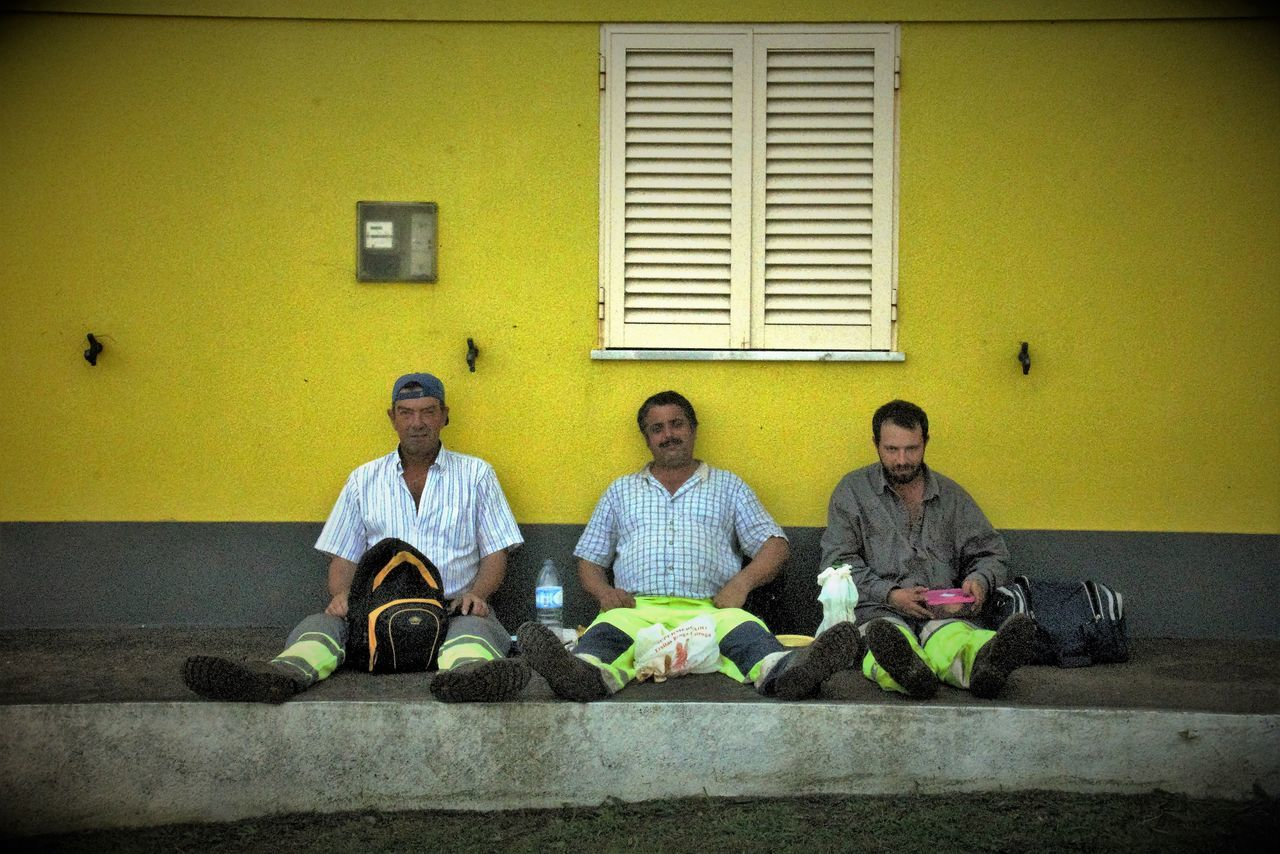Three Men And A Rucksack Blinds Casual Clothing Day Leisure Activity Lifestyles Looking Lunch Box Lunch Break Lunch Time! Person Pooped Rucksack Sitting Streetphotography Three Men Relaxing Threeofakind Triad Wall - Building Feature Warm Days Of Autumn Workers Working Lunch Yellow Wall People And Places Lajes Das Flores Azores