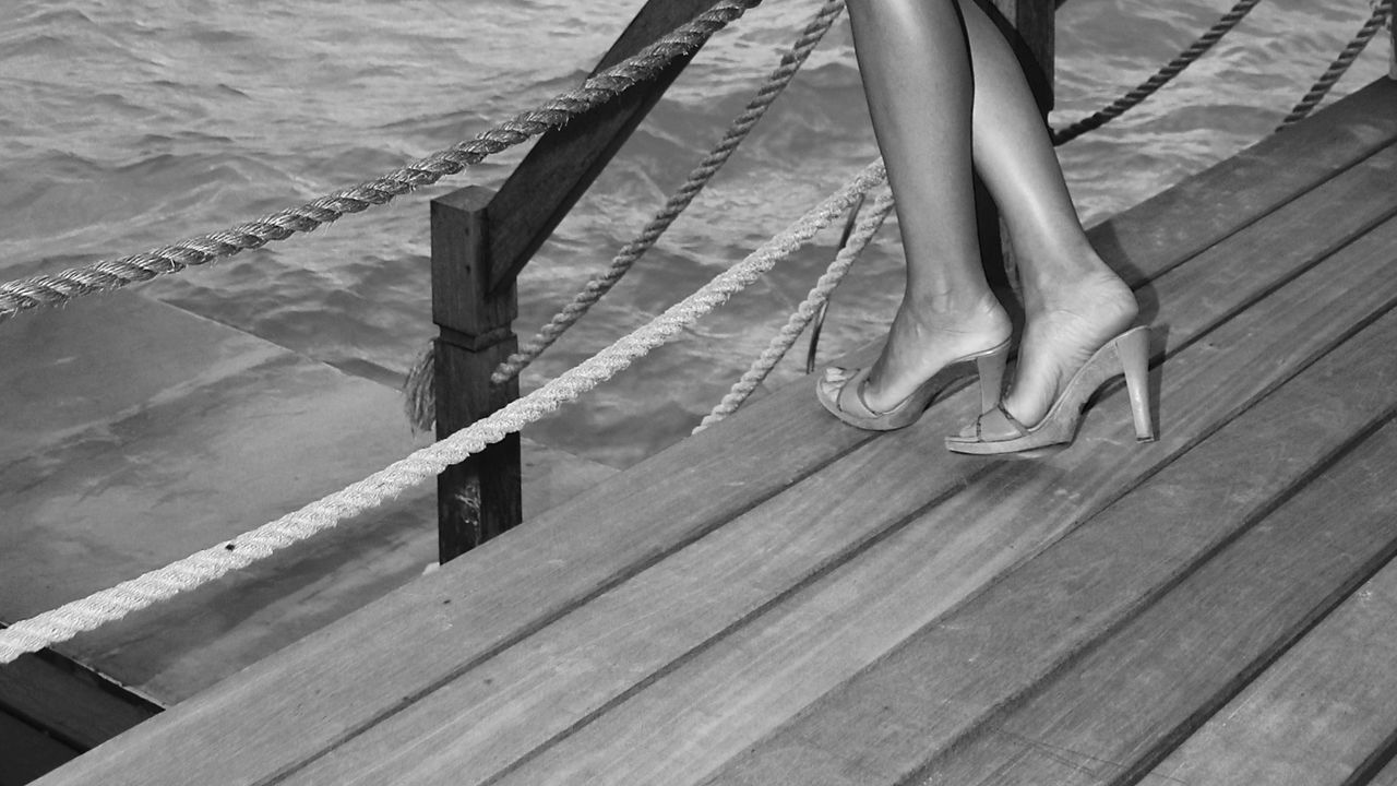 feet on wooden planks against sea Blackandwhite Close-up Deck Design Fashion Feet Female Fine Art Human Body Part Legs Lifestyles Nature Outdoors Pattern People Railing Sea Shoe Standing Water Woman Wooden Wooden Planks