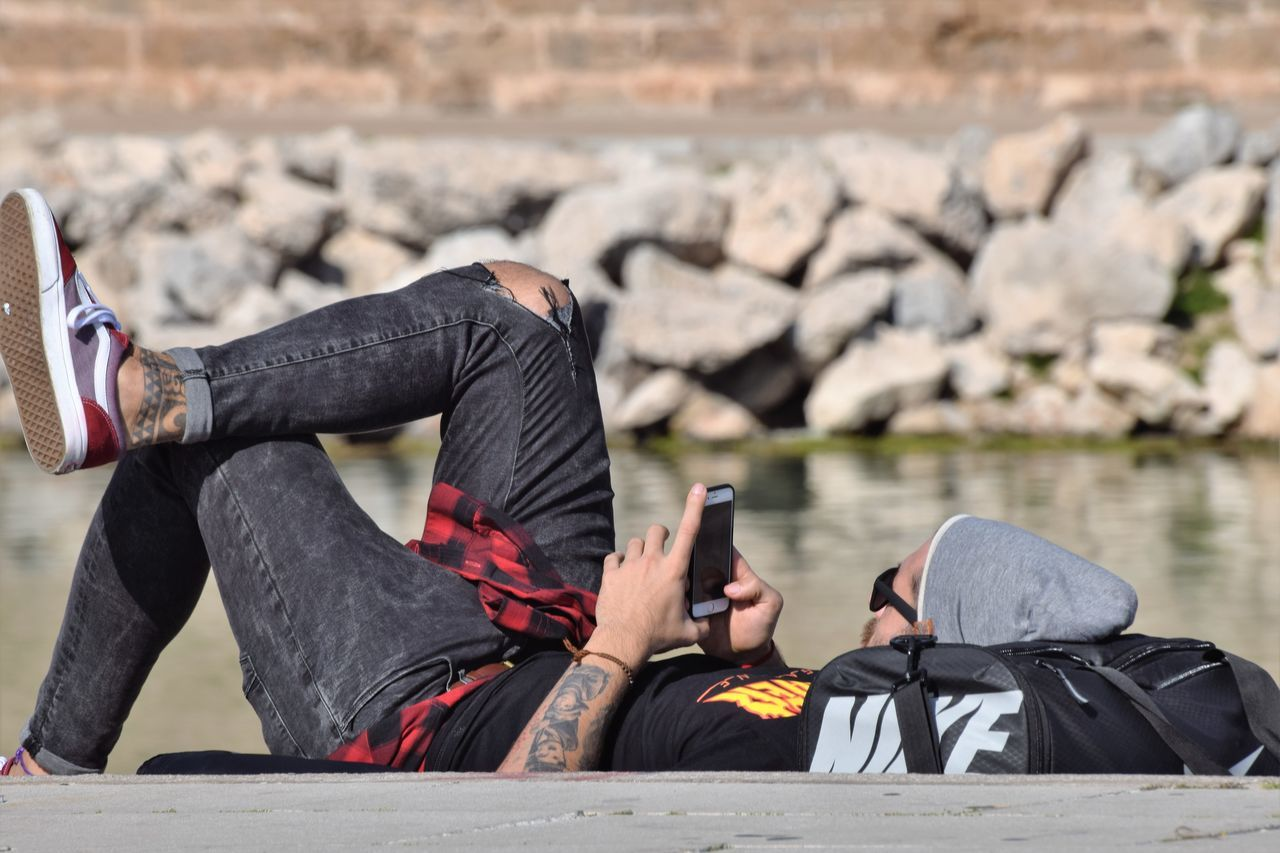 real people, sitting, rock - object, day, one person, outdoors, relaxation, casual clothing, focus on foreground, lifestyles, leisure activity, full length, men, lying down, water, lake, nature, young adult, adult, people