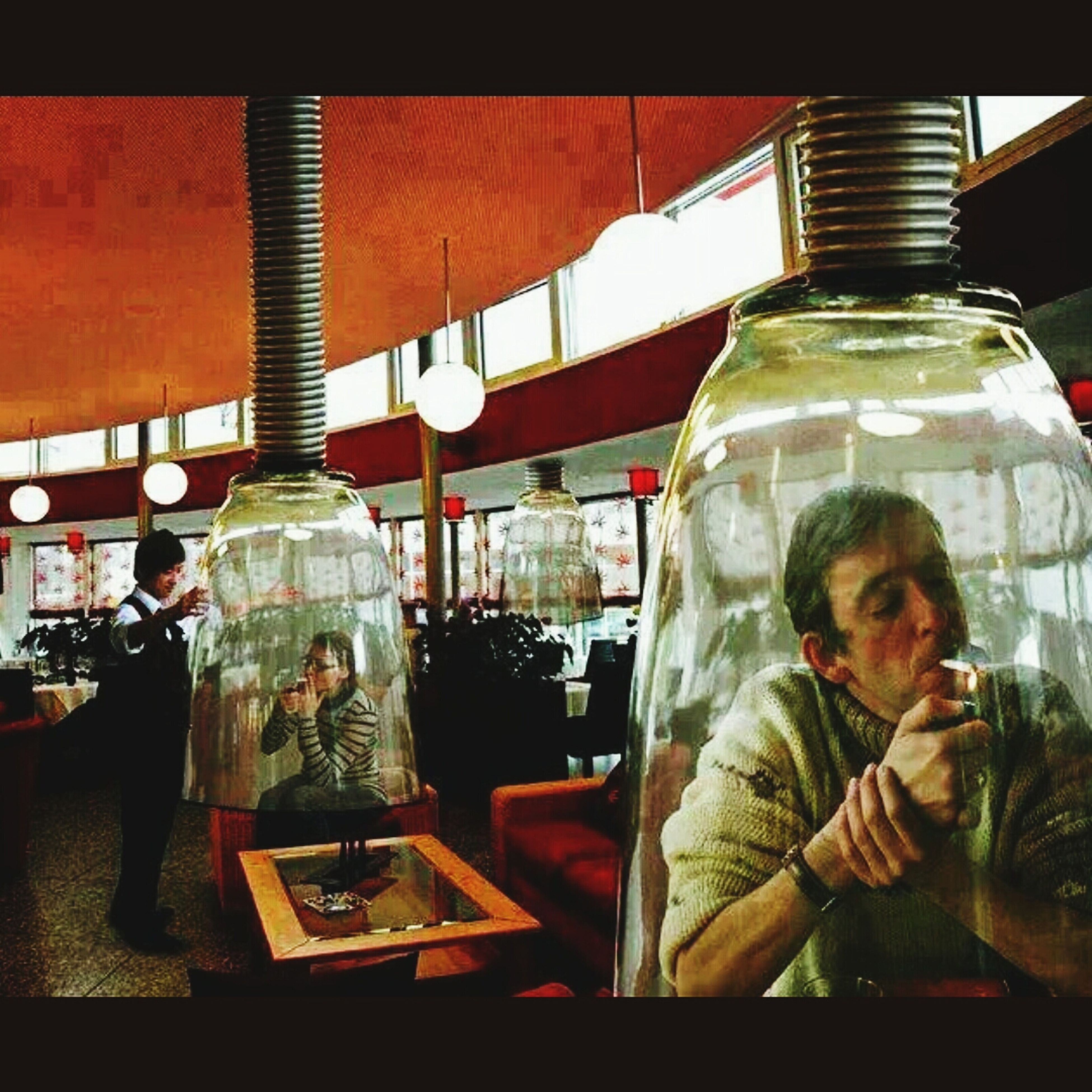 indoors, glass - material, table, religion, celebration, restaurant, spirituality, place of worship, lifestyles, transparent, incidental people, cultures, home interior, human representation, illuminated, men, sitting, tradition