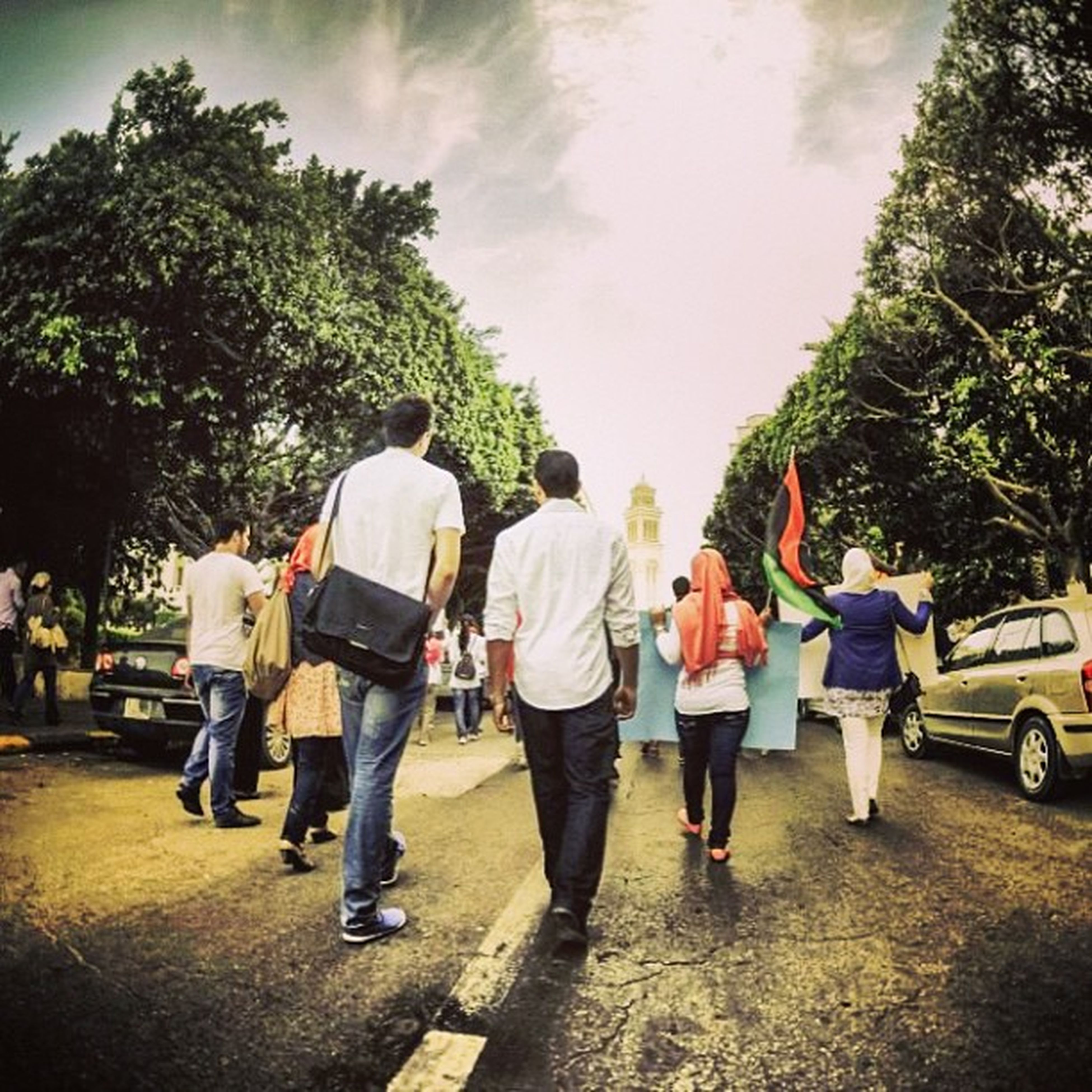 men, person, lifestyles, walking, large group of people, tree, leisure activity, togetherness, street, full length, sky, rear view, road, casual clothing, transportation, medium group of people, group of people, travel, mixed age range
