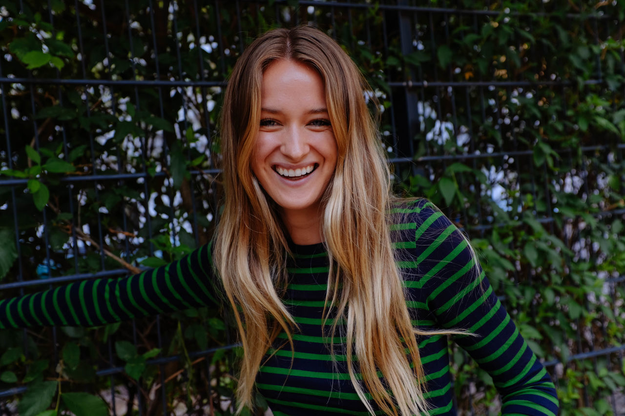 Adult Adults Only Beautiful Woman Casual Clothing Cheerful Close-up Day Front View Happiness Long Hair Looking At Camera Nature One Person One Woman Only One Young Woman Only Only Women Outdoors Portrait Real People Smiling Standing Toothy Smile Tree Young Adult Young Women