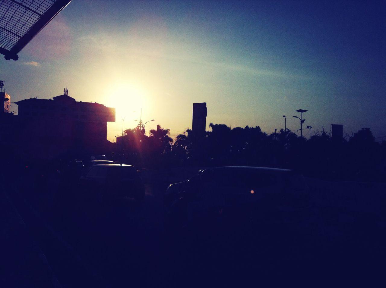 building exterior, architecture, city, built structure, silhouette, sunset, sun, transportation, car, land vehicle, street, sunlight, mode of transport, clear sky, city life, road, sky, lens flare, sunbeam, city street