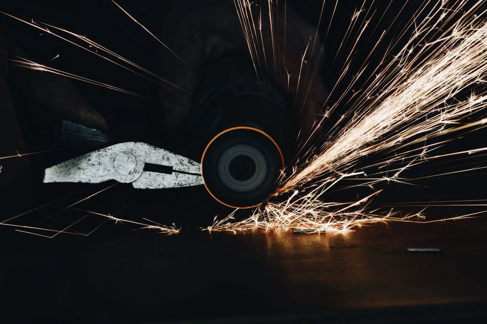 Man using rotary grinder and sparks flying Long Exposure Sparks Motion No People Night Wire Wool Indoors  Metal Industry Circular Saw Rotary Grinder Sparks Flying Sparks On Black Background Industrial Industry Working Hands Industrial Photography Industrial Equipment