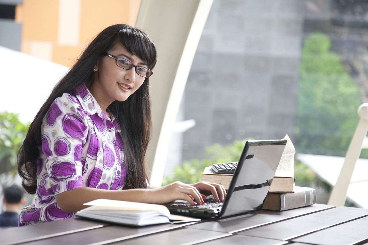 Adult Business Business Finance And Industry Cheerful Communication Computer Desk Education Eyeglasses  Females Internet Laptop People Portrait Smiling Student Technology Typing University University Student Using Laptop Wireless Technology Working Young Adult Young Women