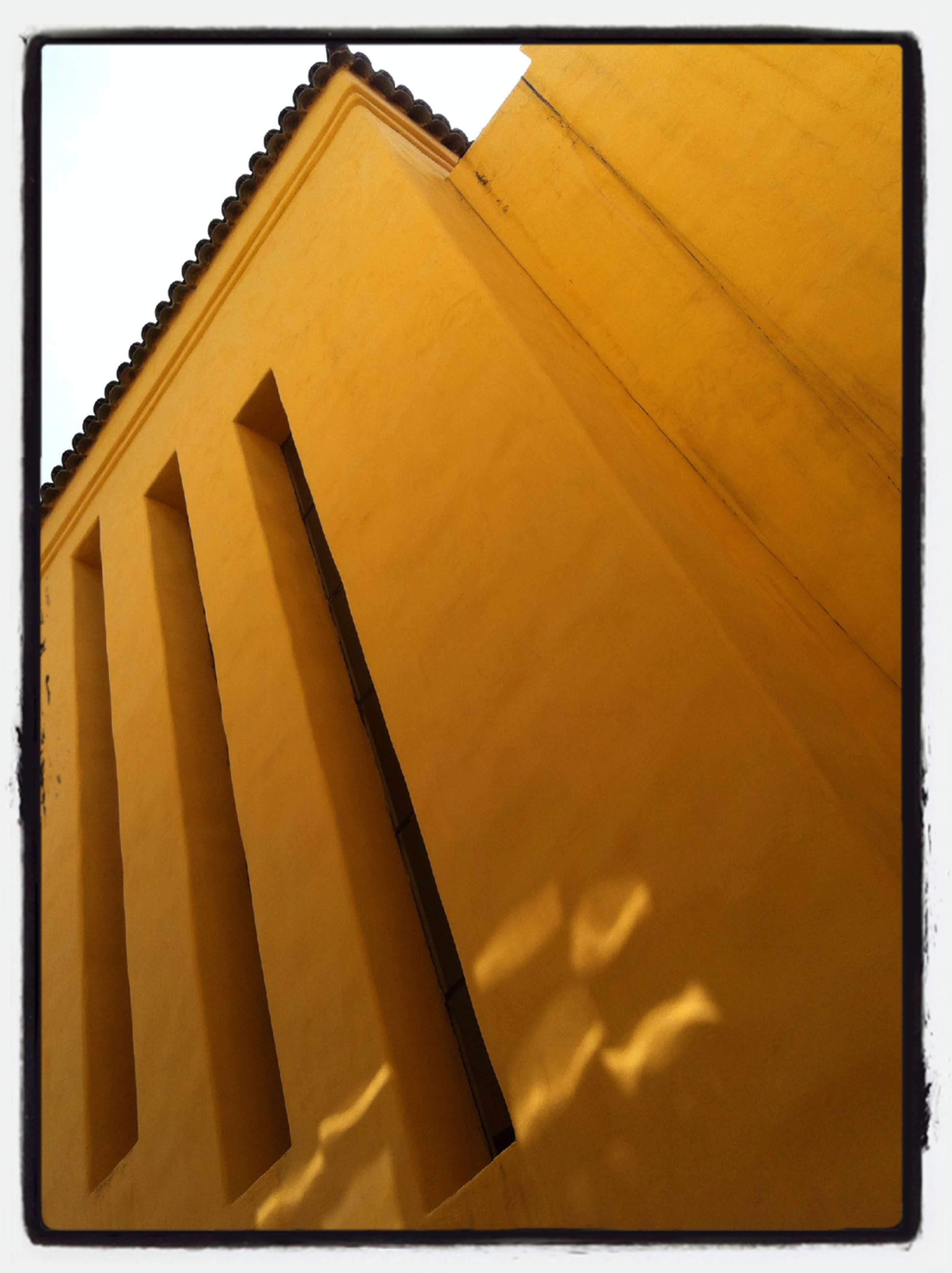 transfer print, auto post production filter, architecture, built structure, low angle view, building exterior, yellow, sky, no people, outdoors, sunlight, day, orange color, pattern, building, wood - material, wall - building feature, window, shadow, tilt