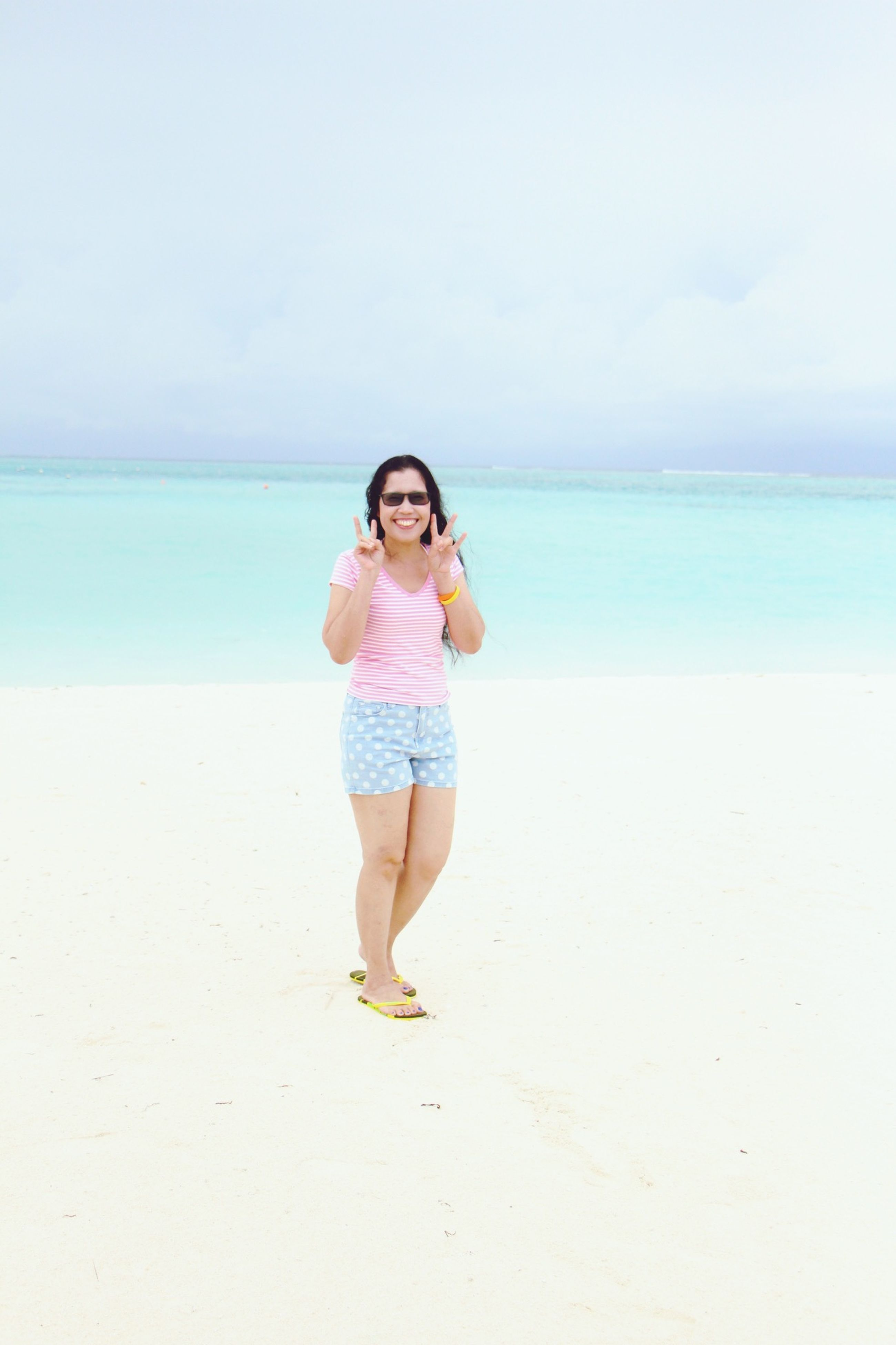 beach, full length, sea, casual clothing, water, horizon over water, lifestyles, shore, leisure activity, standing, person, sand, tranquility, young adult, copy space, tranquil scene, front view, beauty in nature