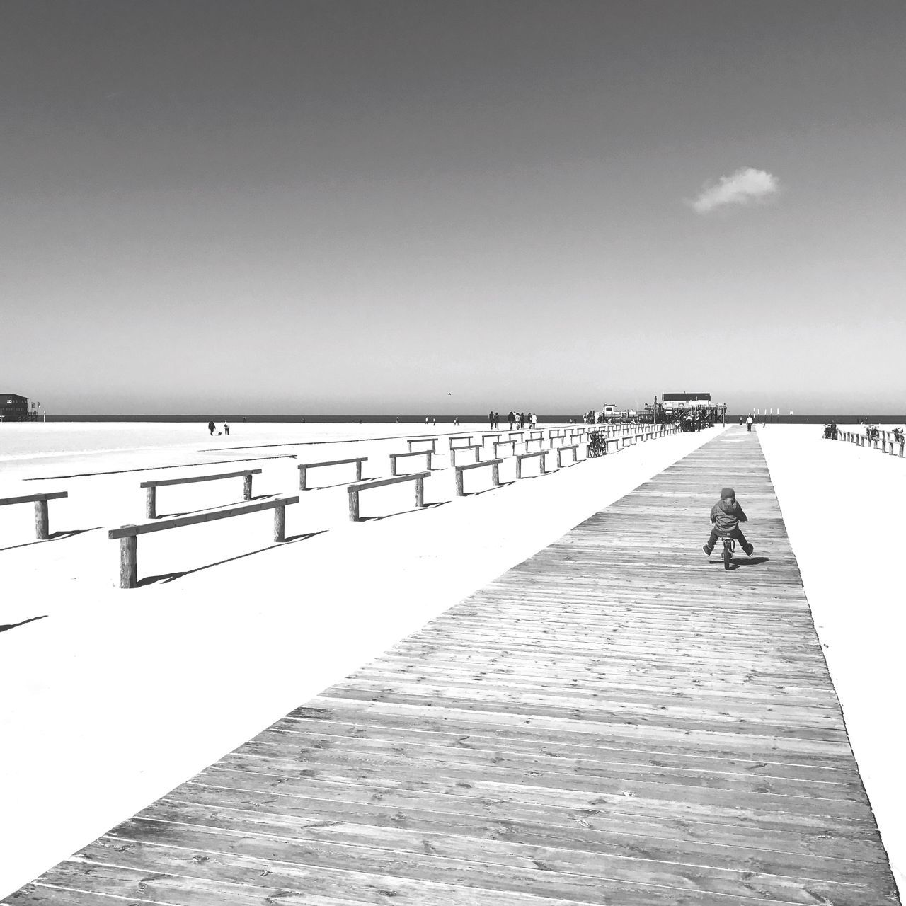 copy space, clear sky, pier, outdoors, full length, walking, sea, day, sunlight, nature, tranquility, beach, sky, real people, one person, beauty in nature, women, men, wood paneling, water, horizon over water, people